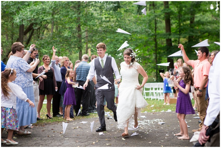 bride and groom run through paper airplane sendoff at Historic Meeting House of New Garden