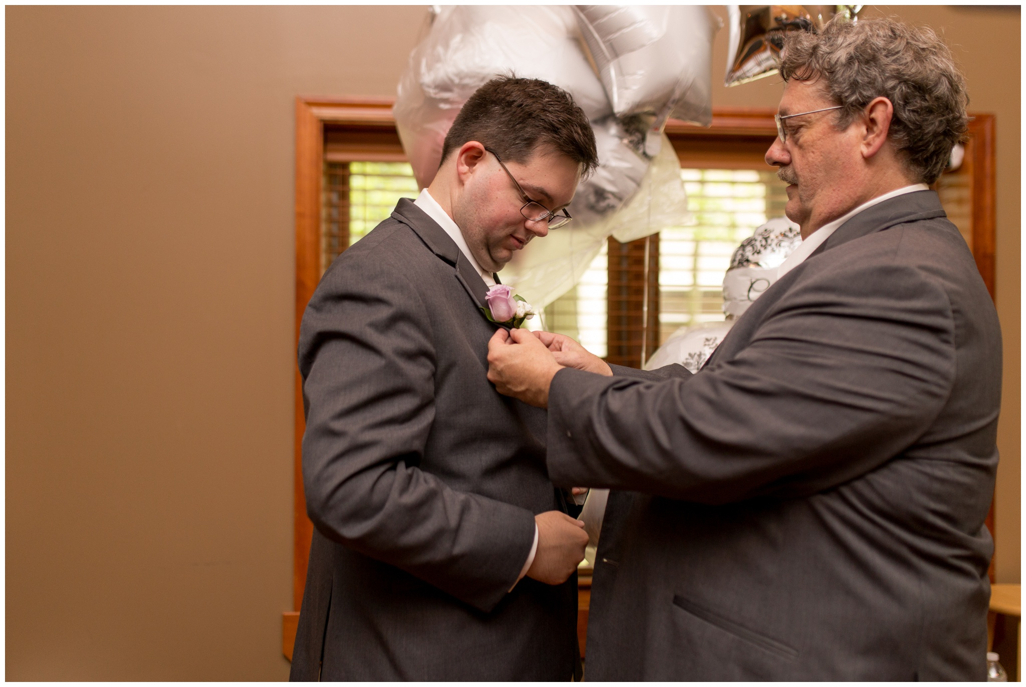 father of groom puts boutonniere on groom before wedding at Crossroads Community Church in Kokomo Indiana