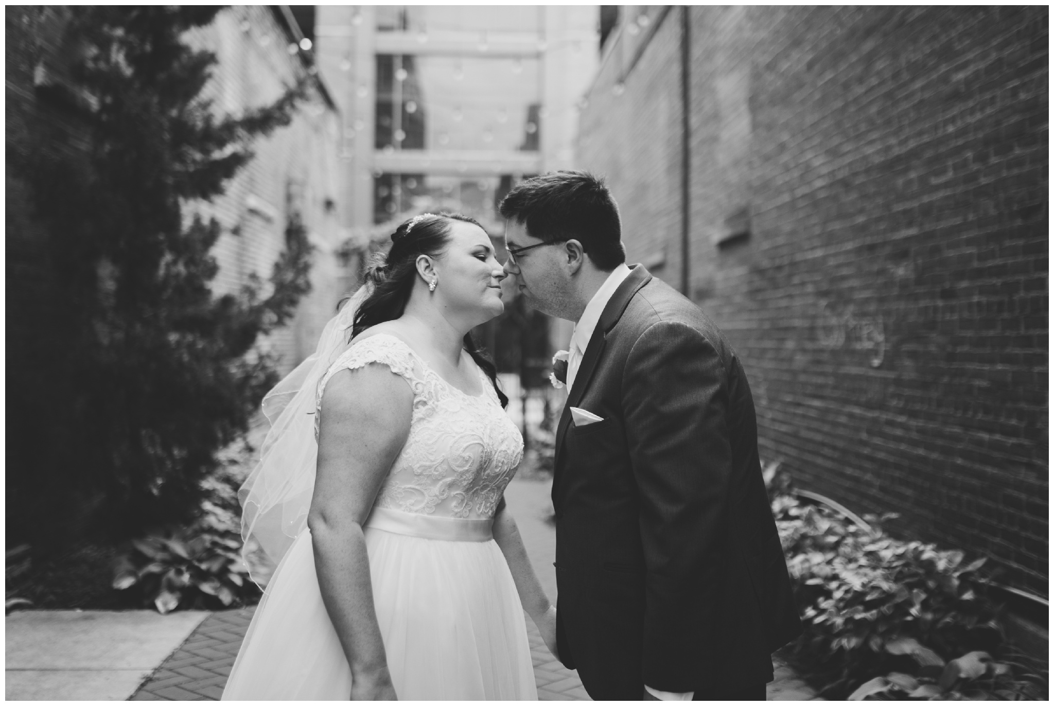 bride and groom kissing before wedding in downtown Kokomo