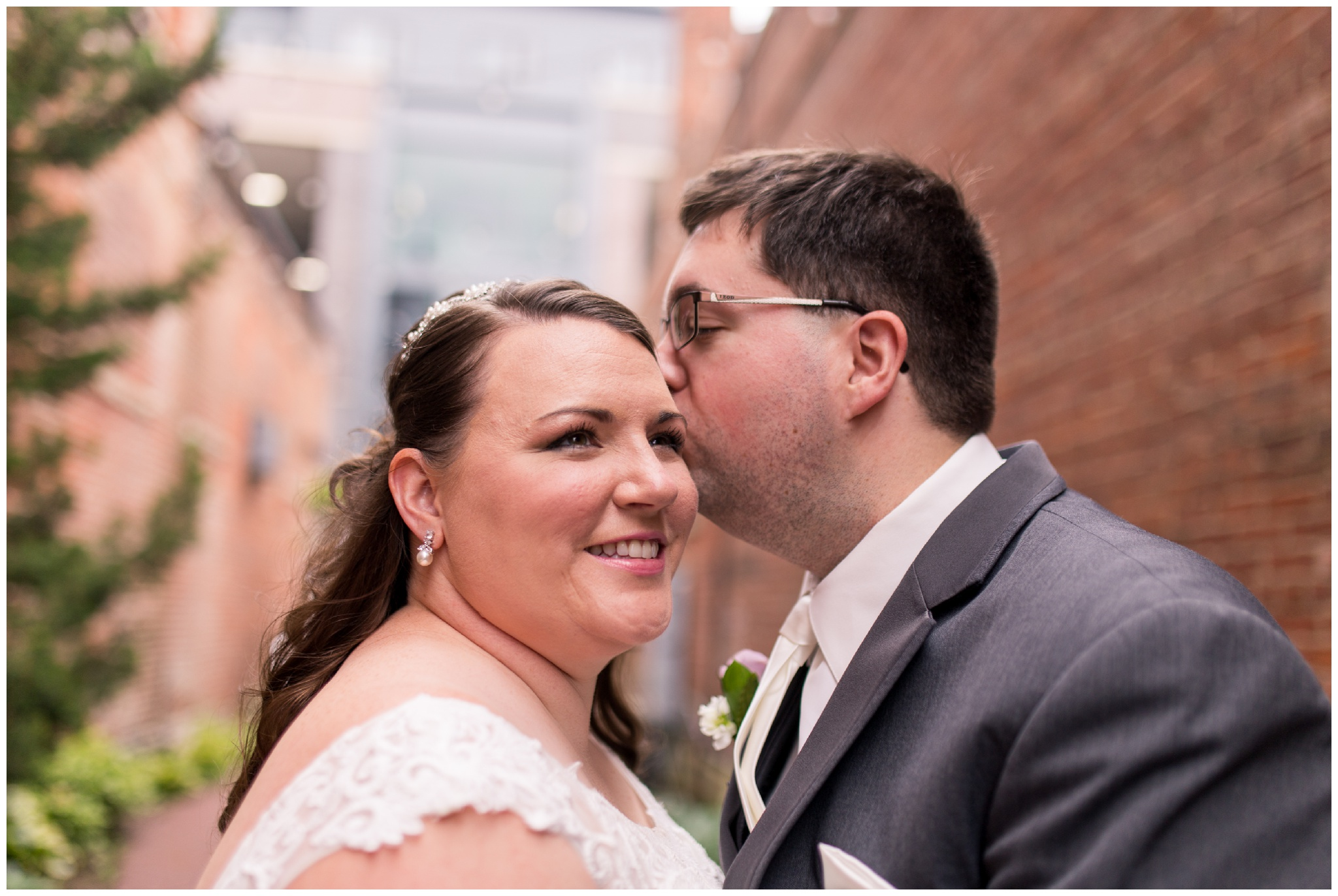 groom kisses bride's forehead before wedding in downtown Kokomo