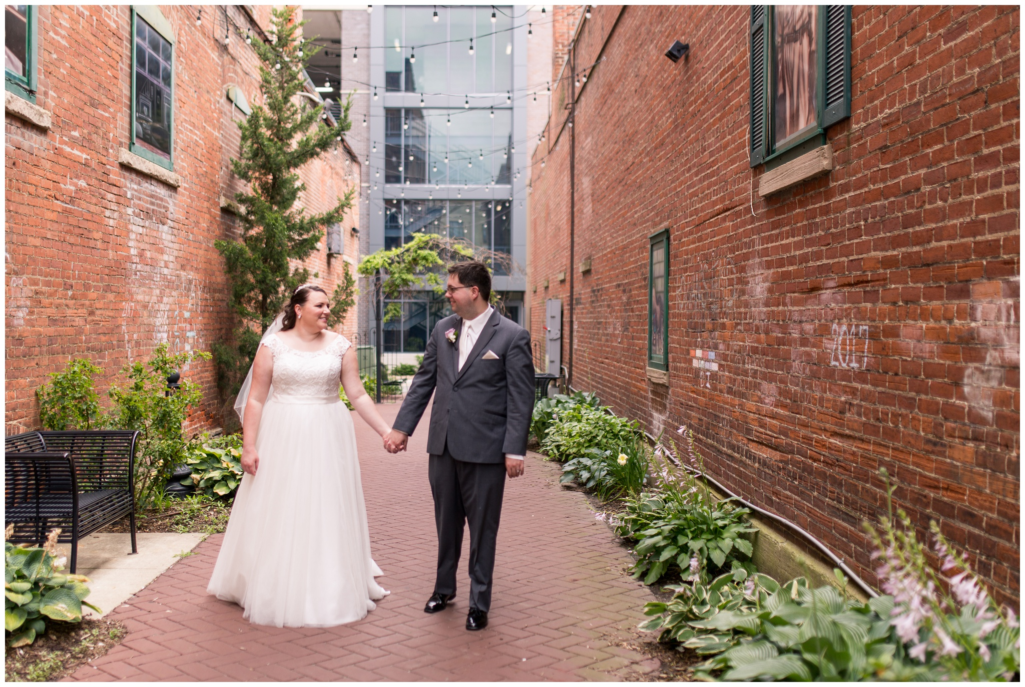 bride and groom hold hands and walk through downtown Kokomo alley