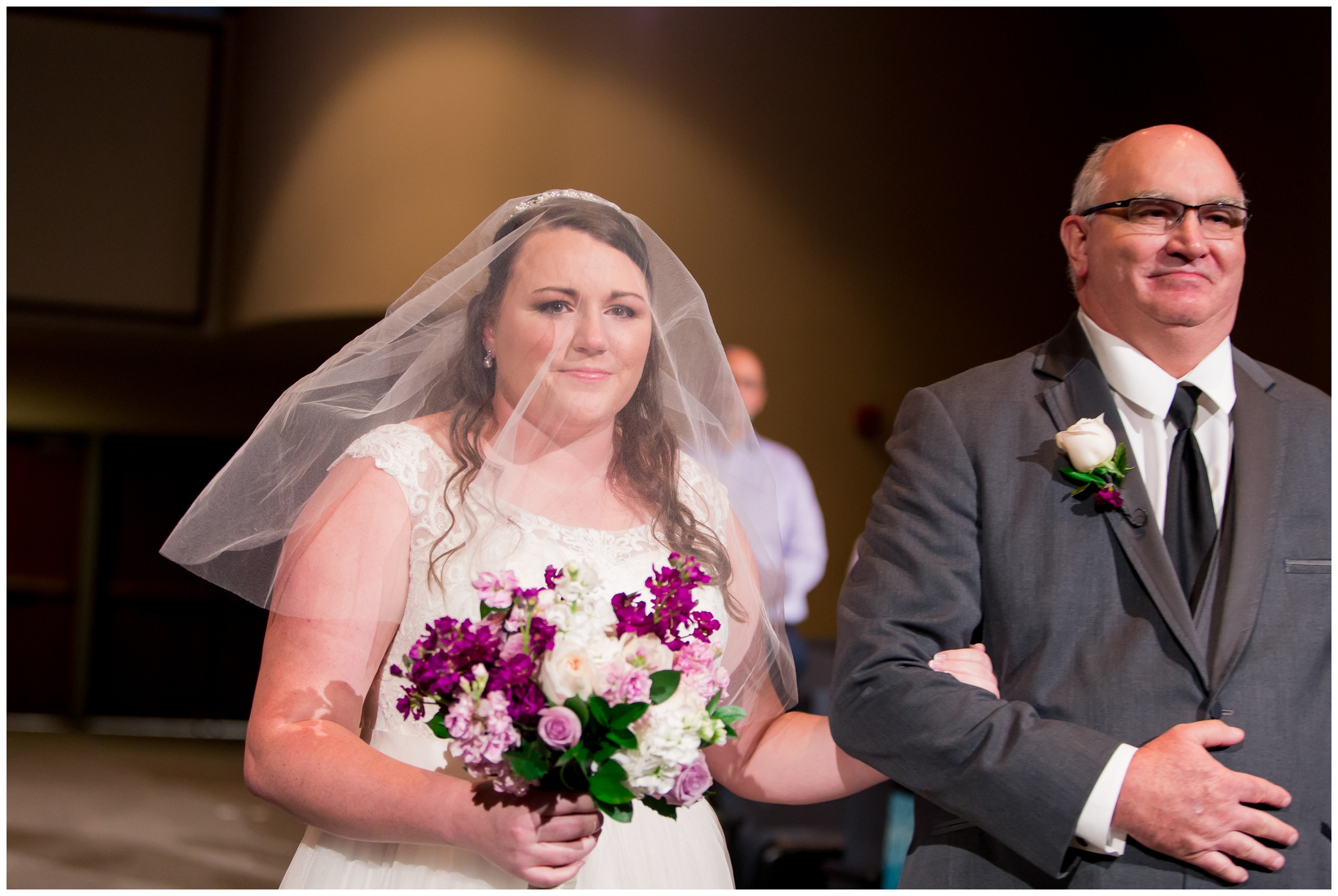 bride holding father's arm walking down the aisle during wedding ceremony at Crossroads Community Church in Kokomo Indiana