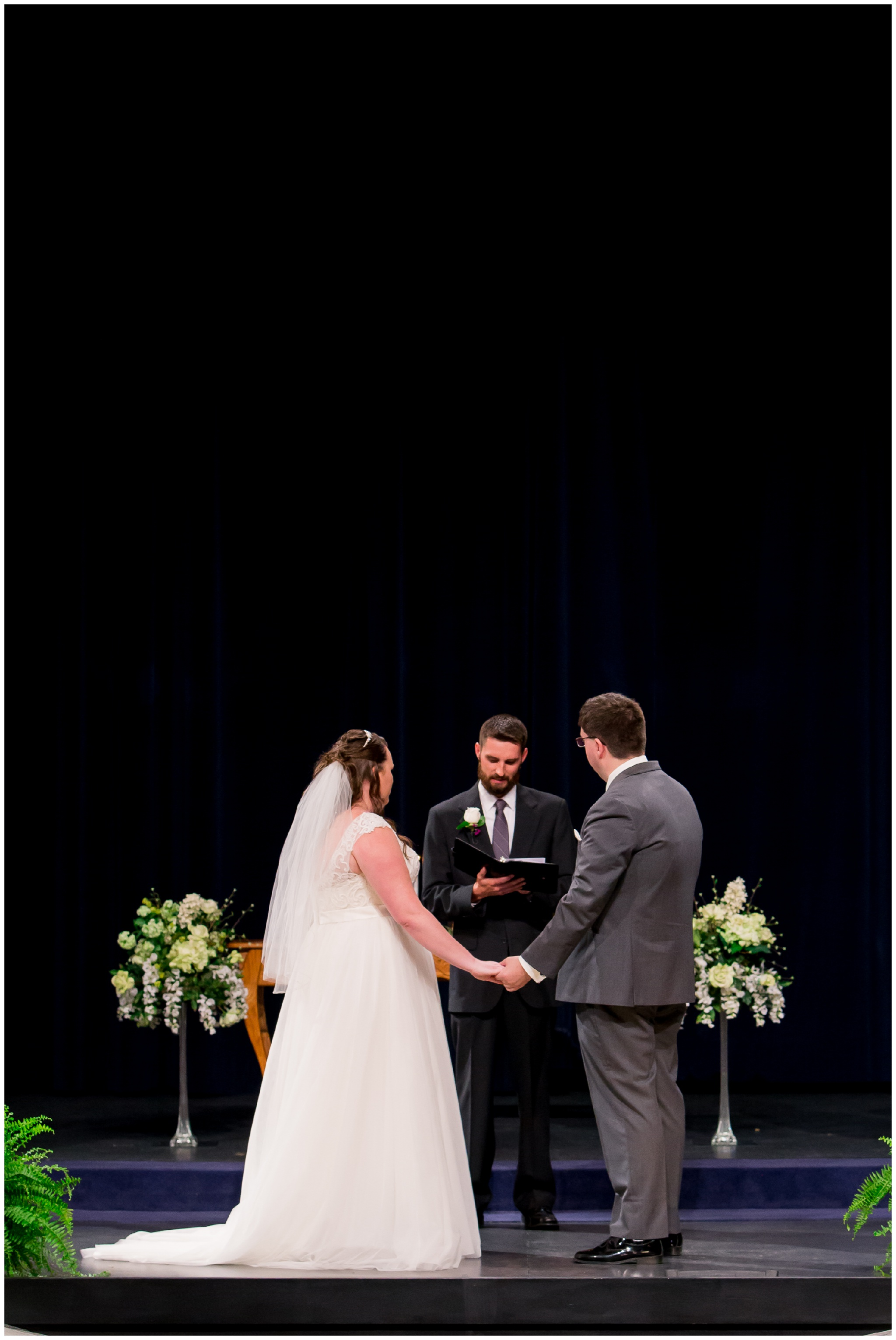 bride and groom hold hands during wedding ceremony at Crossroads Community Church in Kokomo Indiana