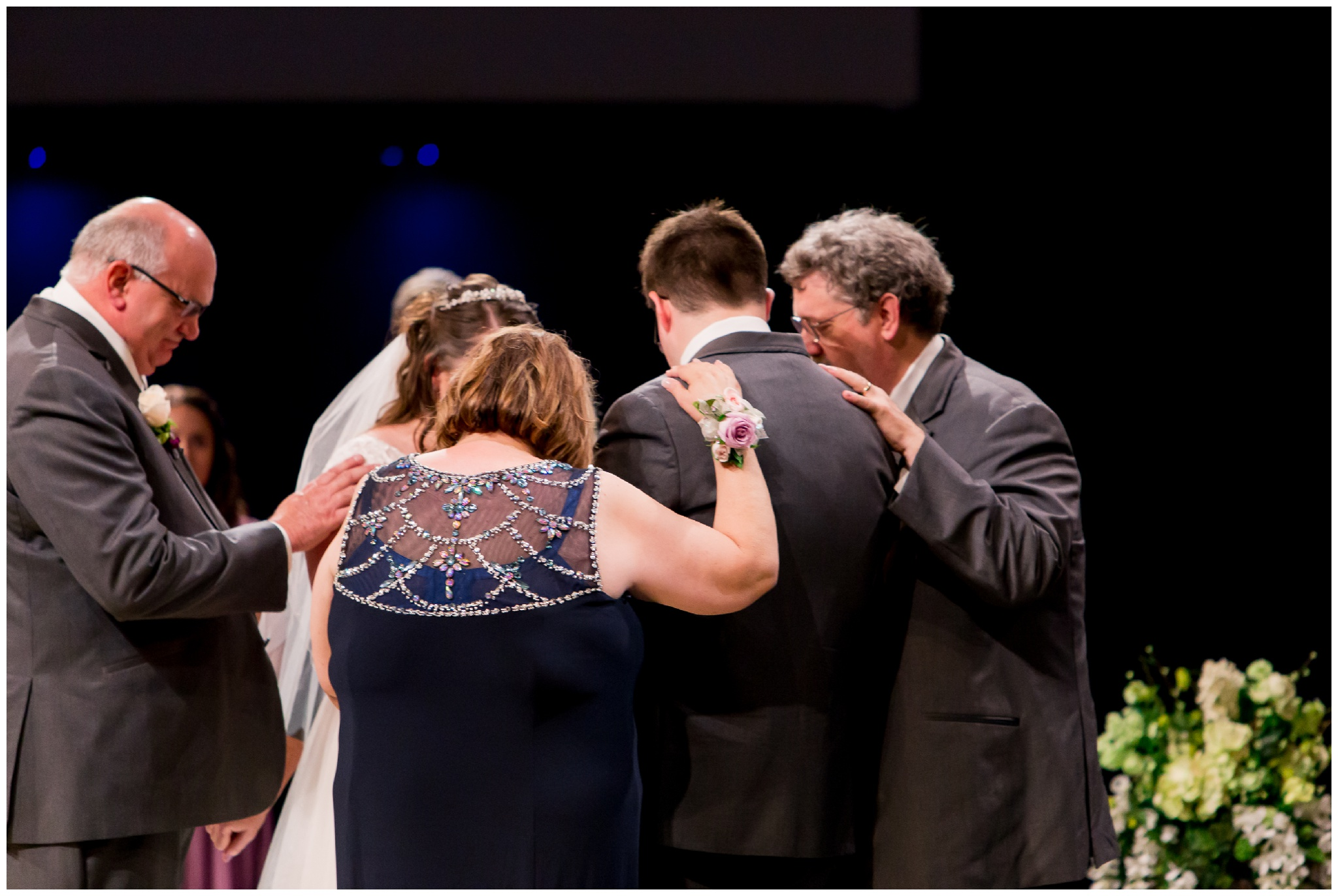 bride and groom's parents pray over couple during wedding ceremony at Crossroads Community Church in Kokomo Indiana