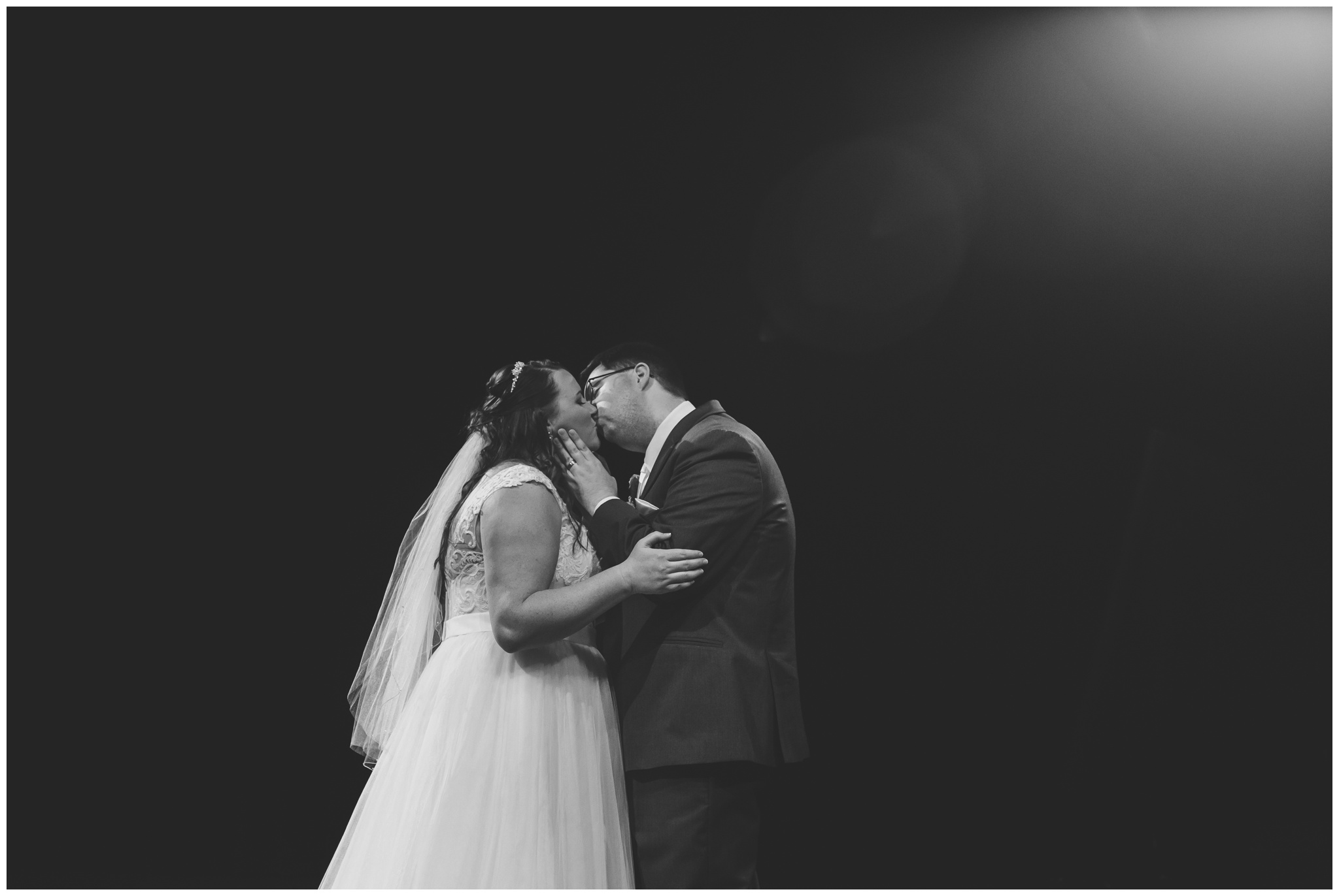 bride and groom kiss on stage at Crossroads Community Church after ceremony in Kokomo Indiana