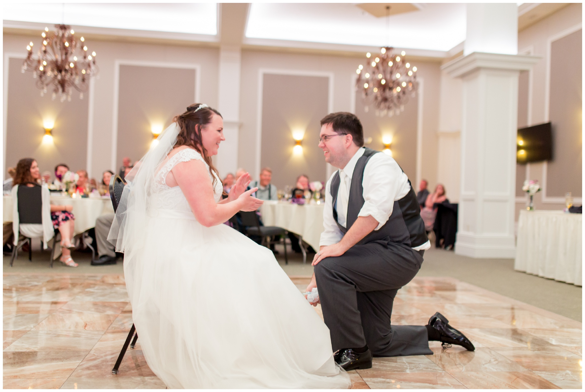 groom removes bride's garter at Bel Air Events Kokomo