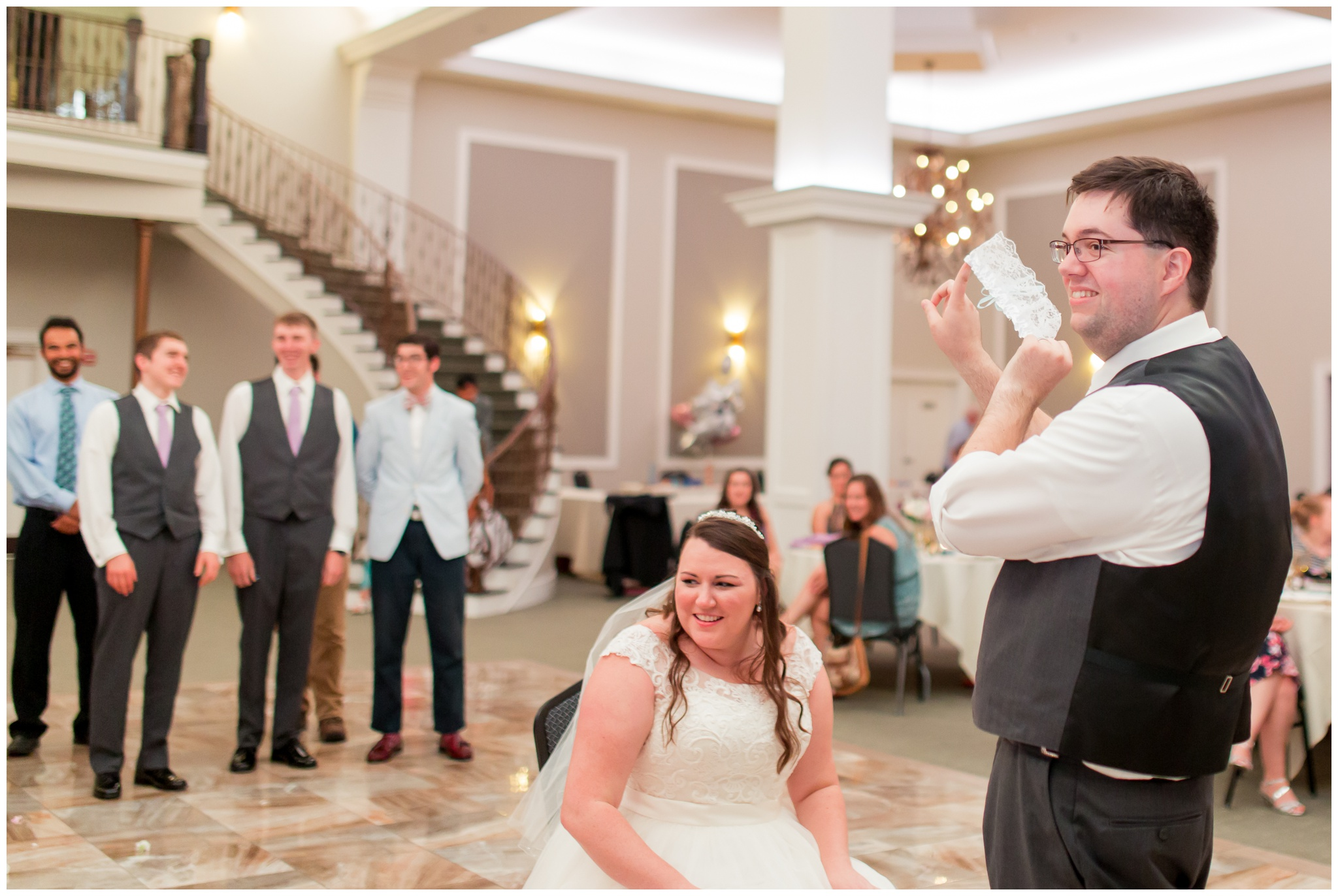 groom tosses garter at Bel Air Events Kokomo wedding reception