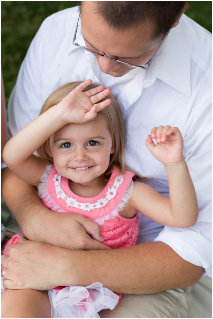 Child sitting on dad's lap during Indianapolis backyard family portrait session