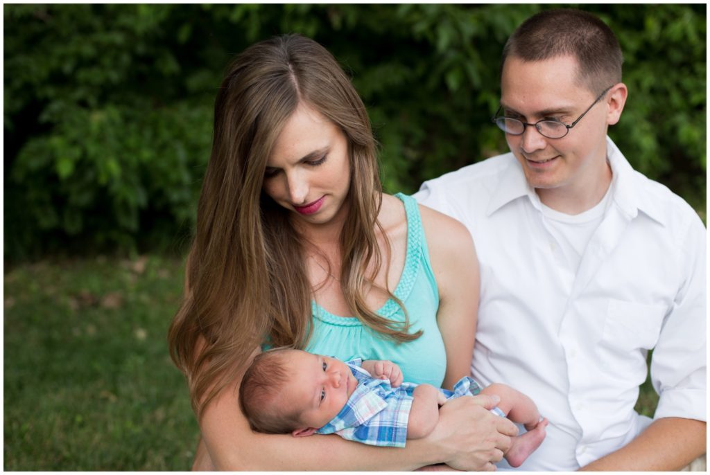 Mother and father looking at newborn during Indianapolis backyard family portrait session