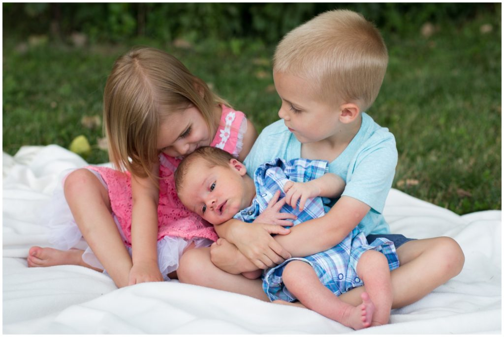 Children holding and kissing baby during Indianapolis backyard family portrait session
