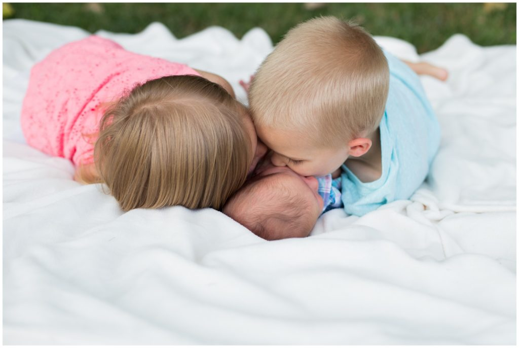 Children kissing newborn during Indianapolis backyard family portrait session