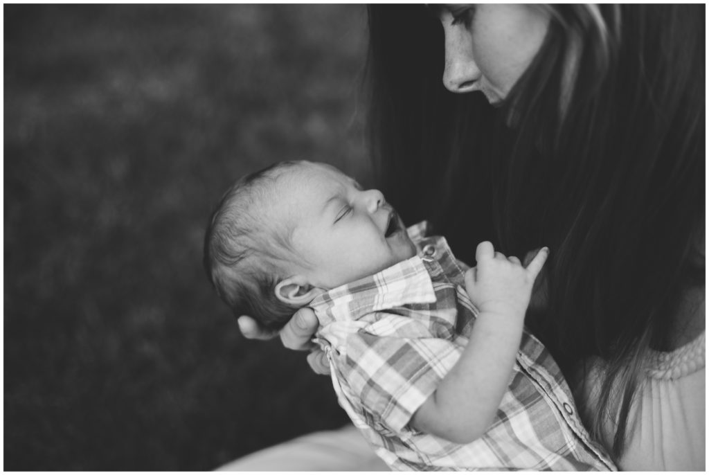 Mother holding newborn close during Indianapolis backyard family portrait session