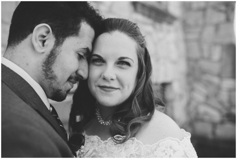 Bride looking at camera with groom's forehead caressing cheek