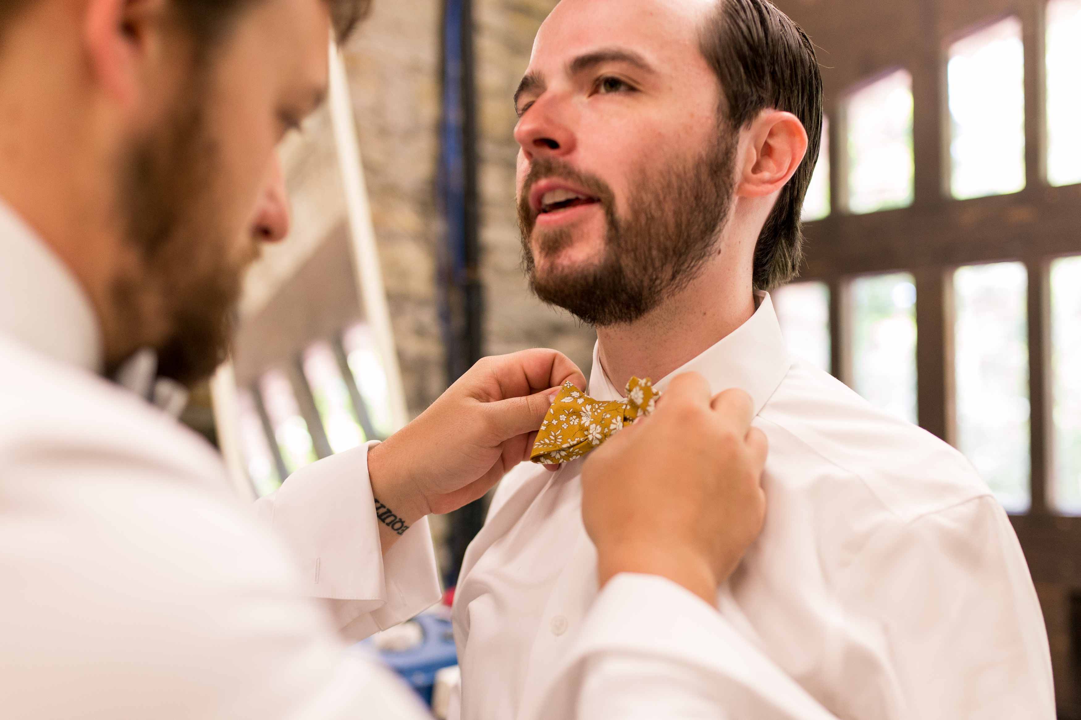 groom putting on bowtie at Minnetrista Cultural Center