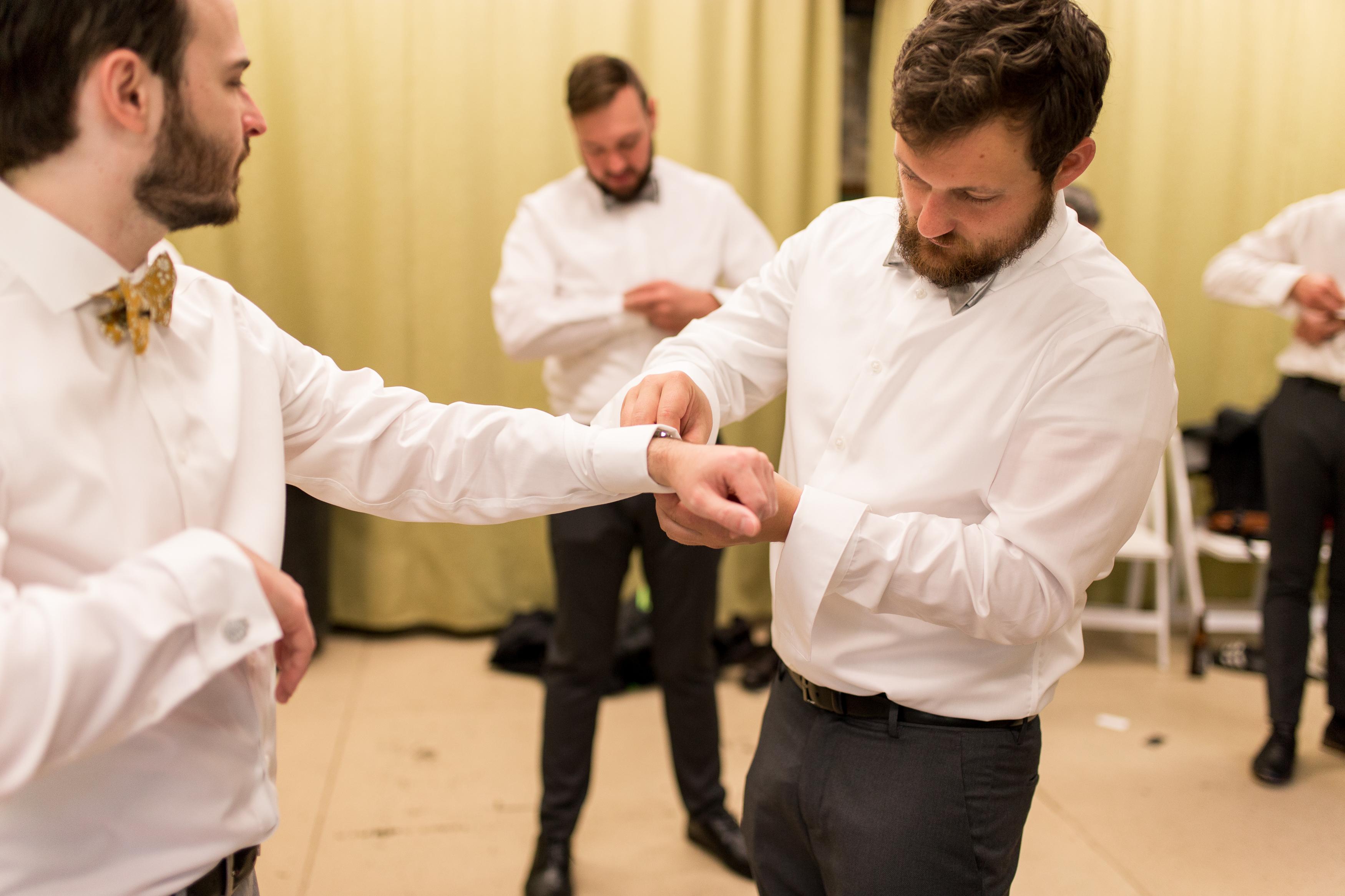 groomsman putting on groom's cufflinks for Muncie Indiana wedding