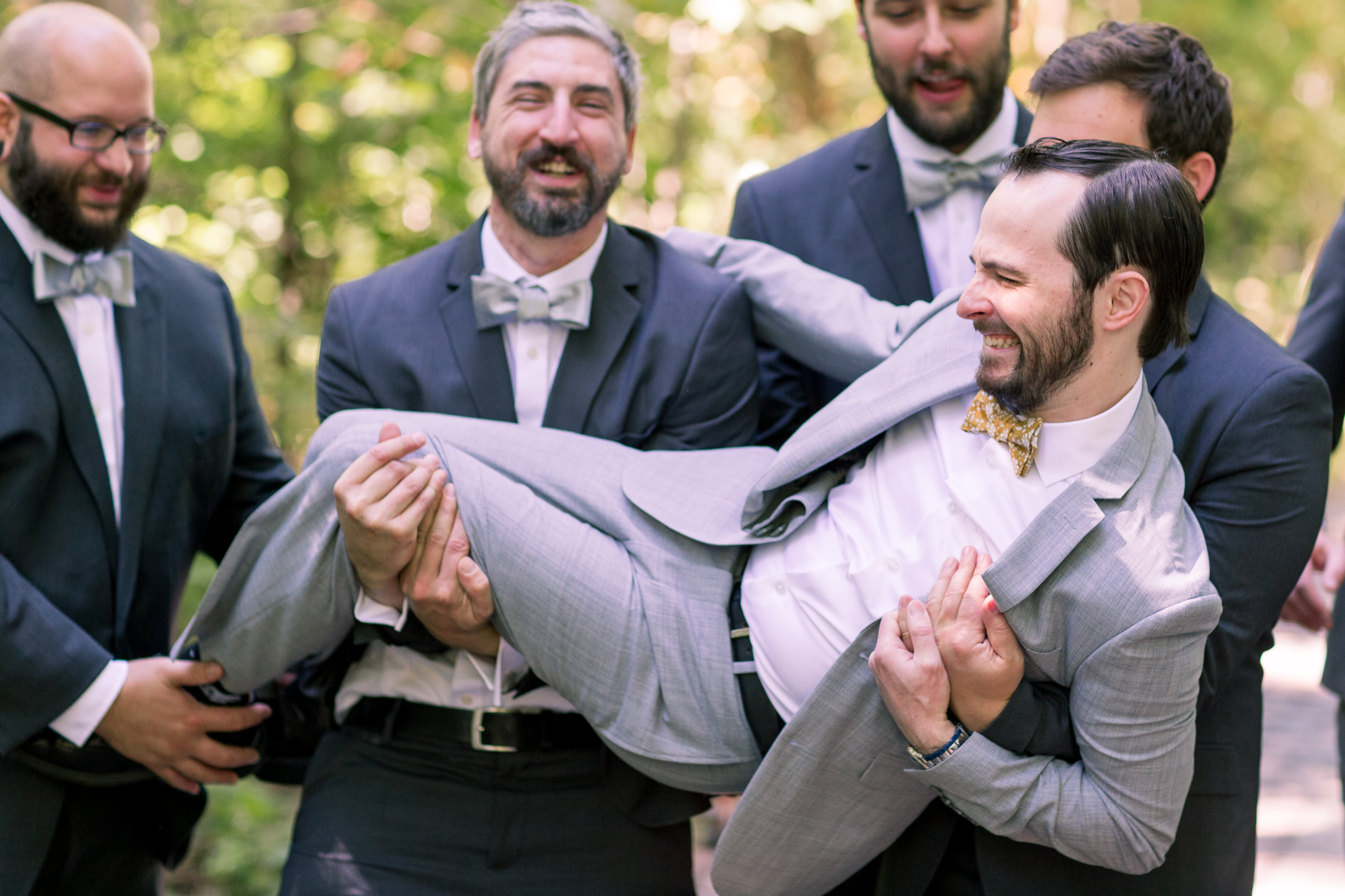 groomsmen lifting groom during portraits at Minnetrista Cultural Center in Muncie Indiana