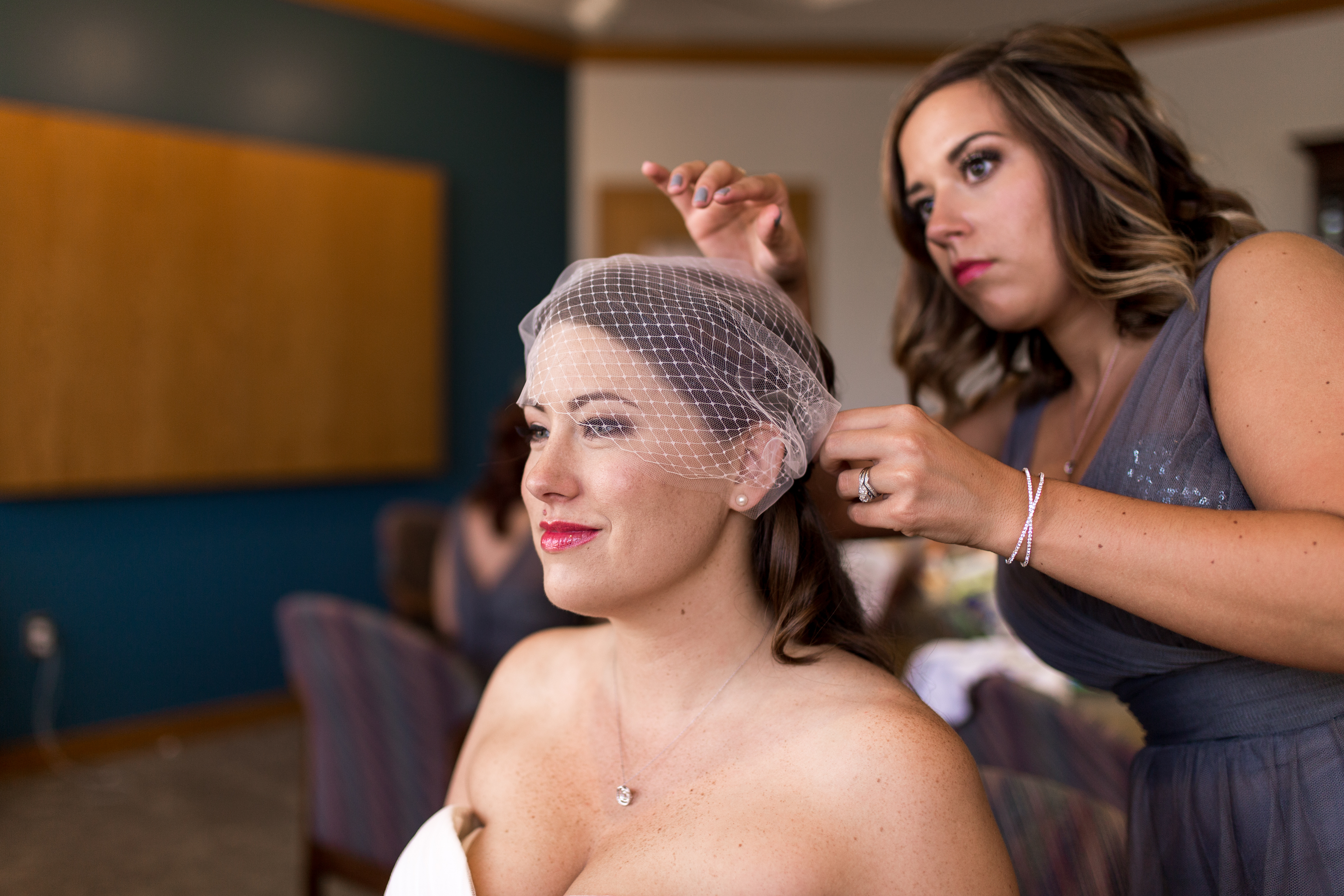 matron of honor putting birdcage veil on bride for Muncie Indiana wedding