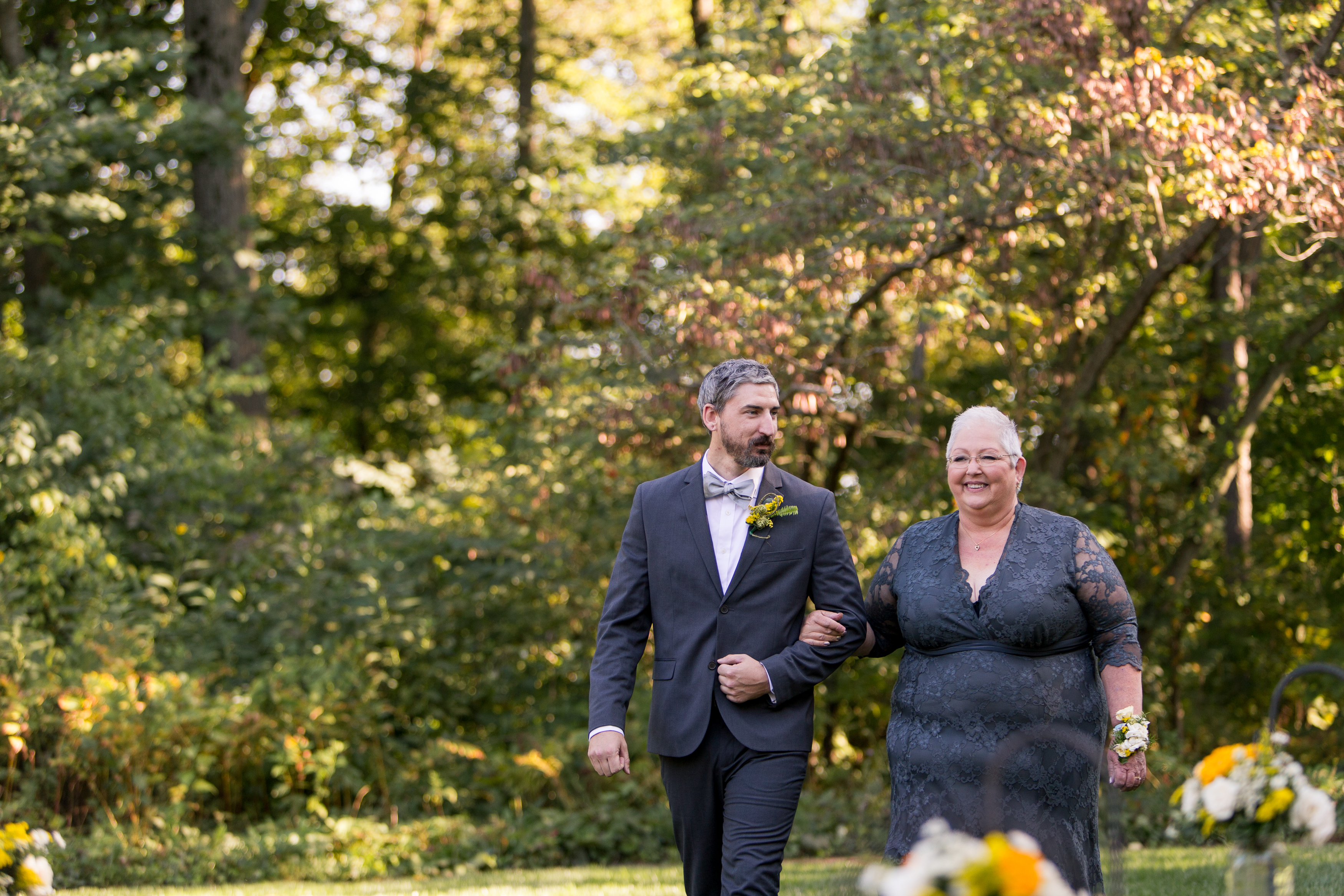 mother of bride with son walking into wedding ceremony at Minnetrista