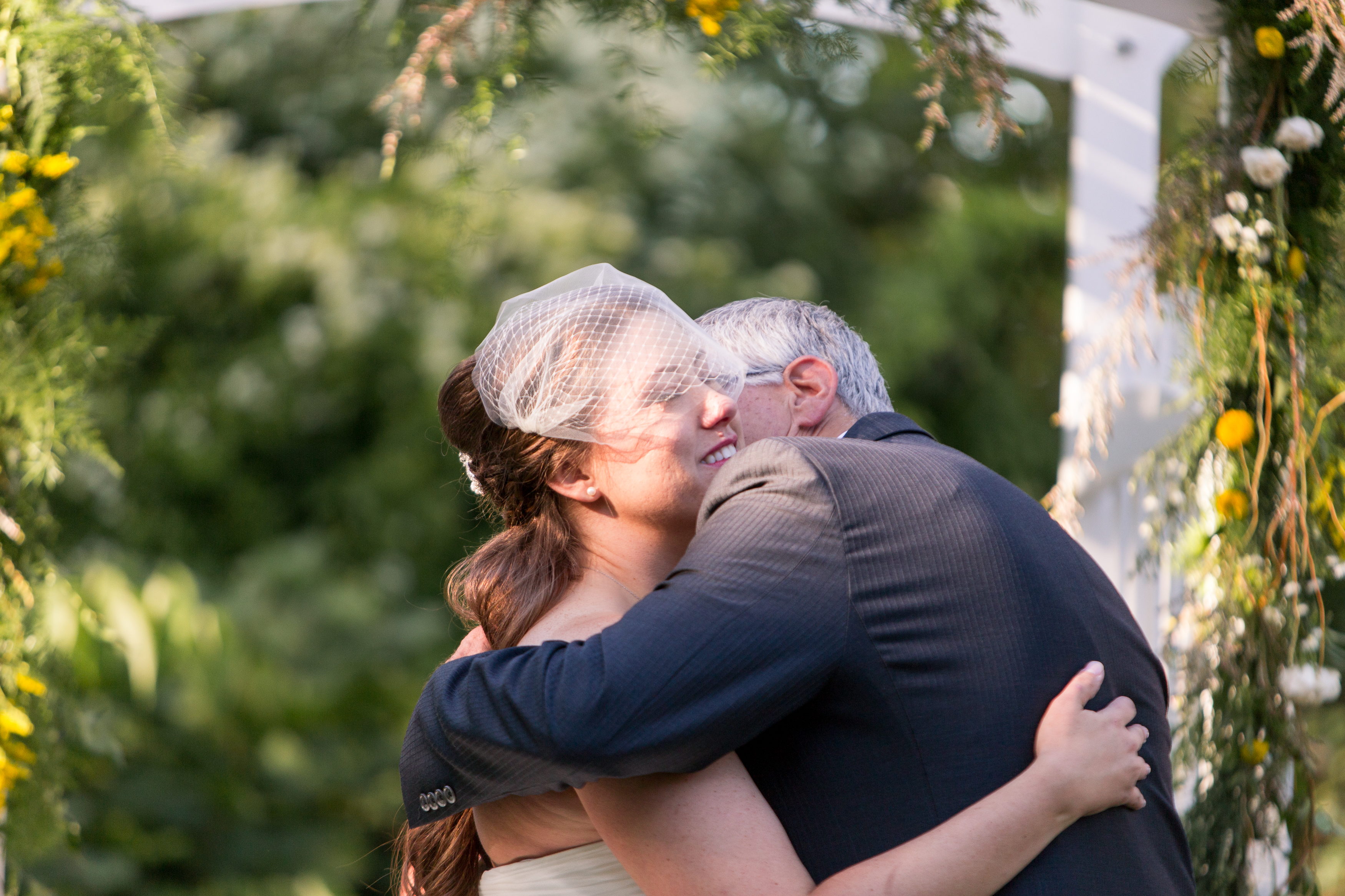 father of bride hugs bride during wedding ceremony at Minnetrista in Muncie Indiana
