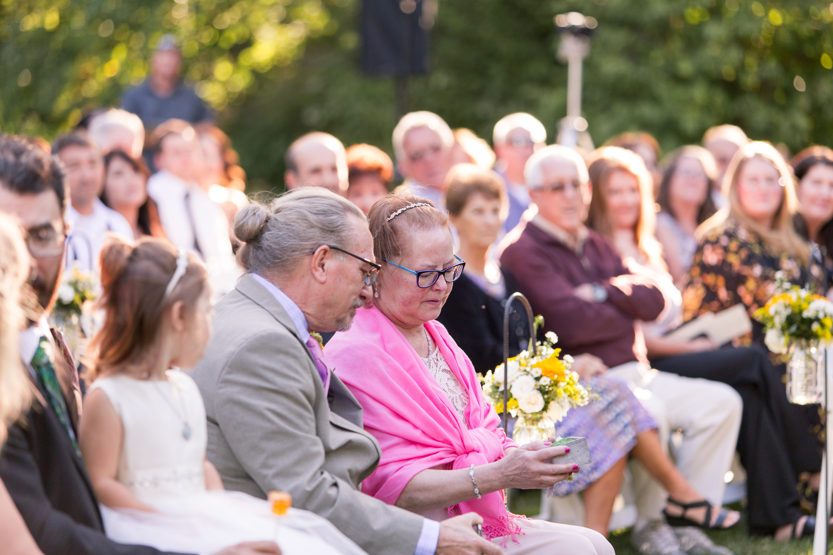 mother and father of groom warming rings during wedding ceremony at Minnetrista Oakhurst Formal Garden in Muncie Indiana