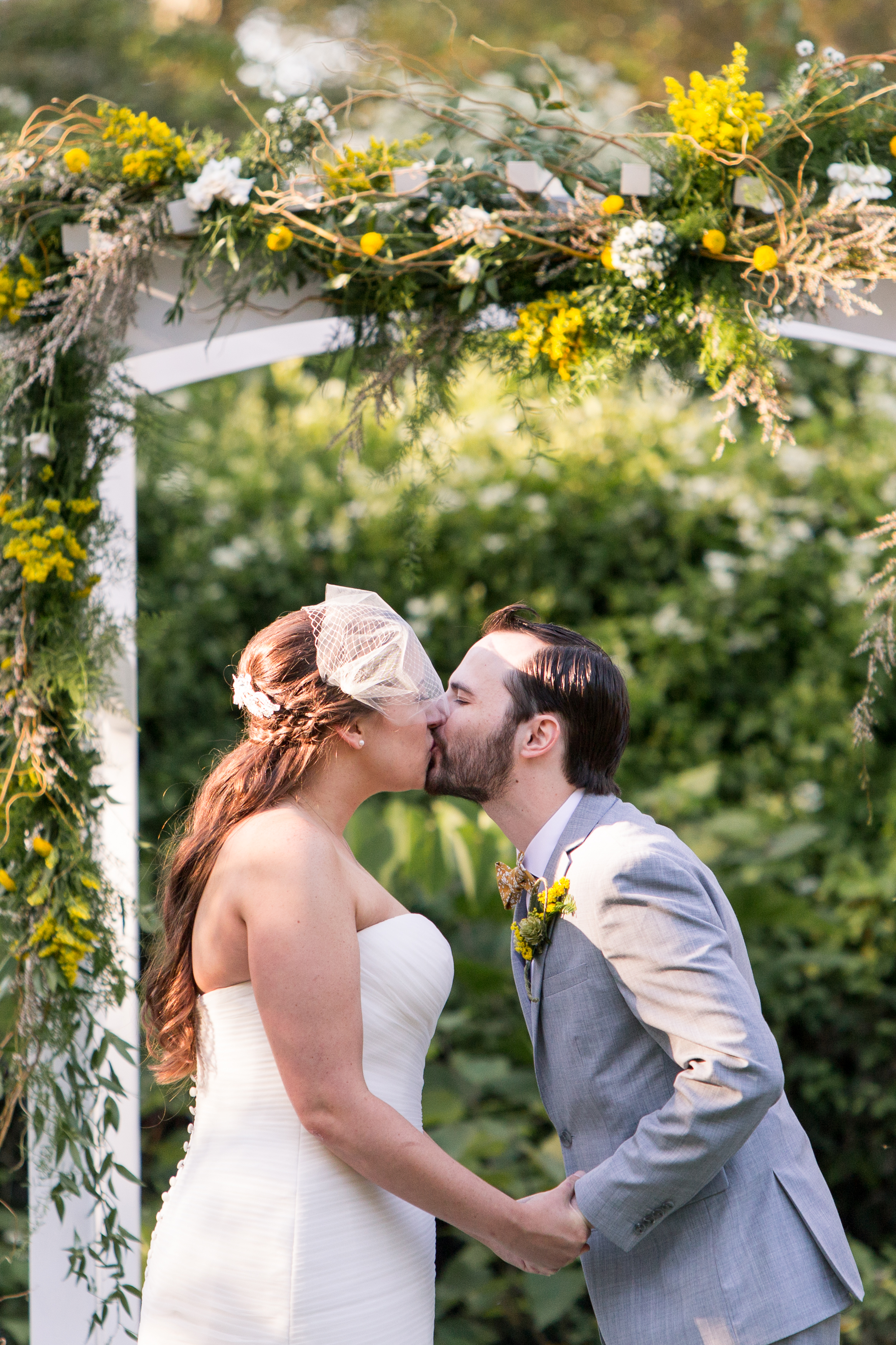 bride and groom first kiss during Muncie Indiana wedding at Minnetrista