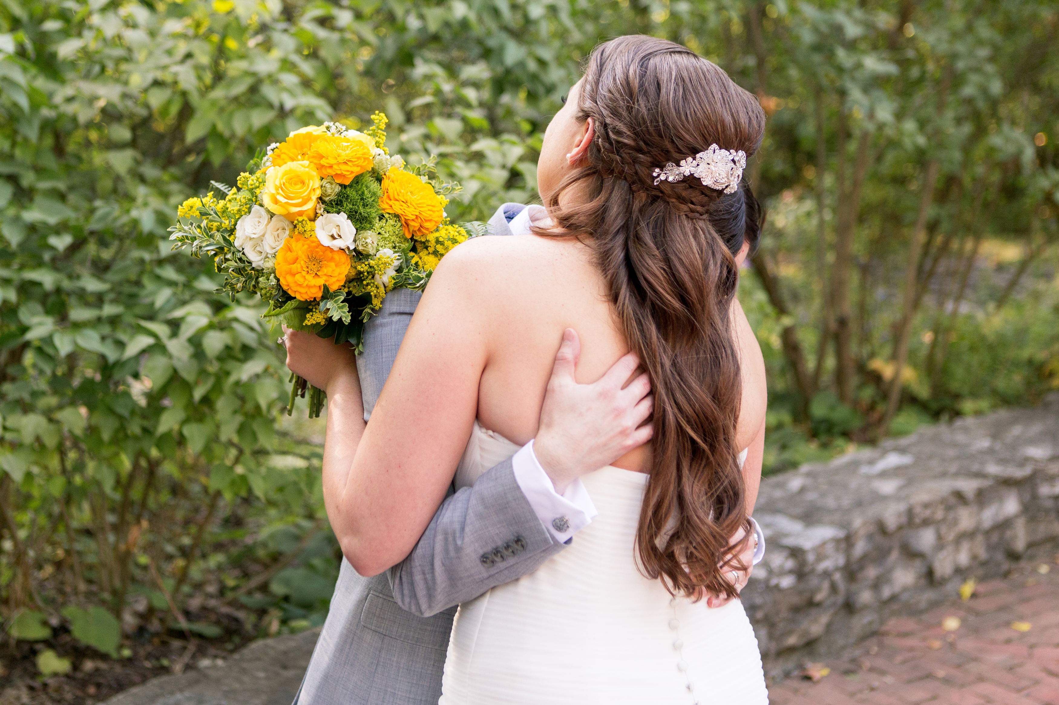 bride and groom hug after ceremony in Oakhurst Formal Gardens at Minnetrista in Muncie Indiana