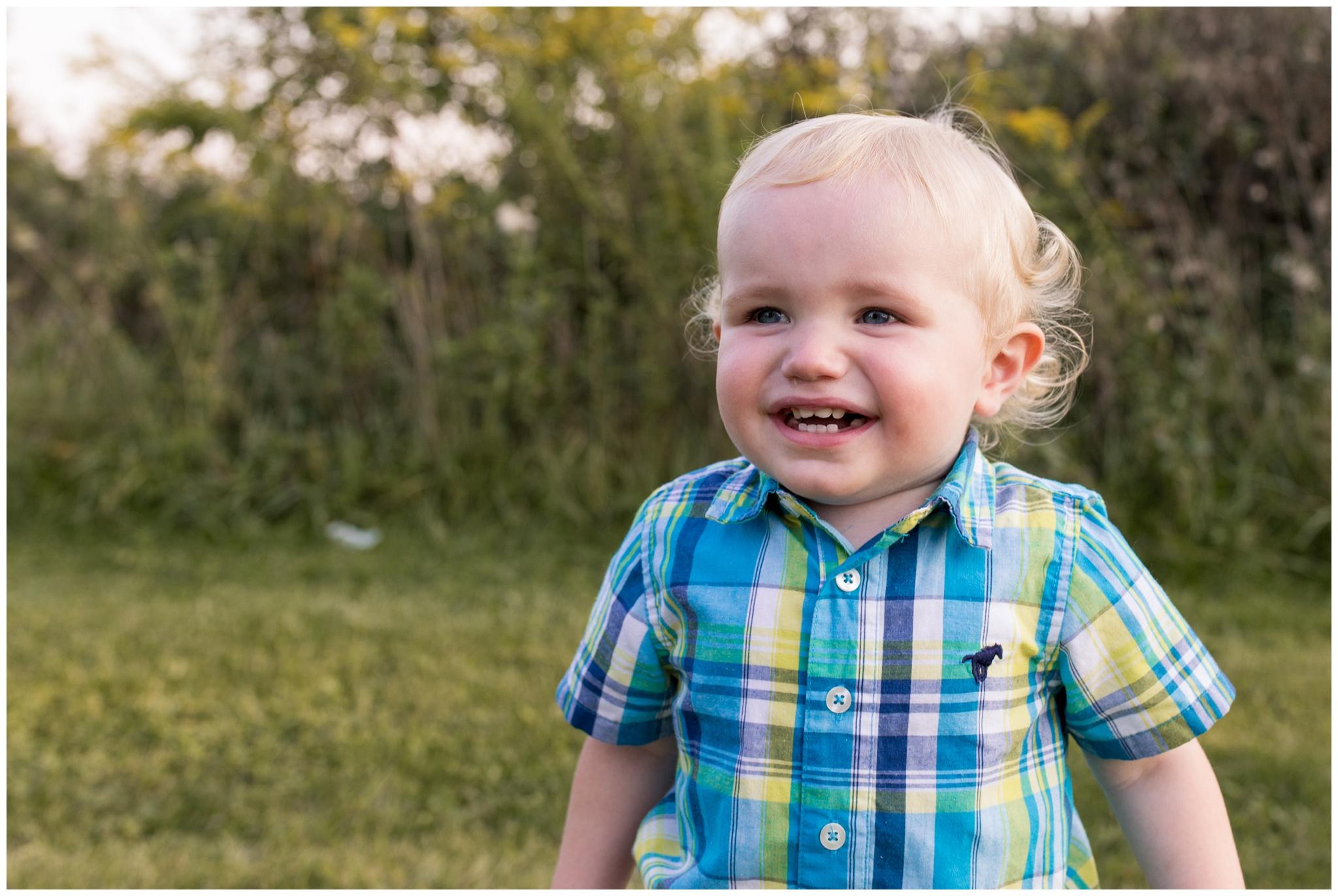 little boy smiling during family photos at Wildcat Creek Reservoir Park in Kokomo Indiana
