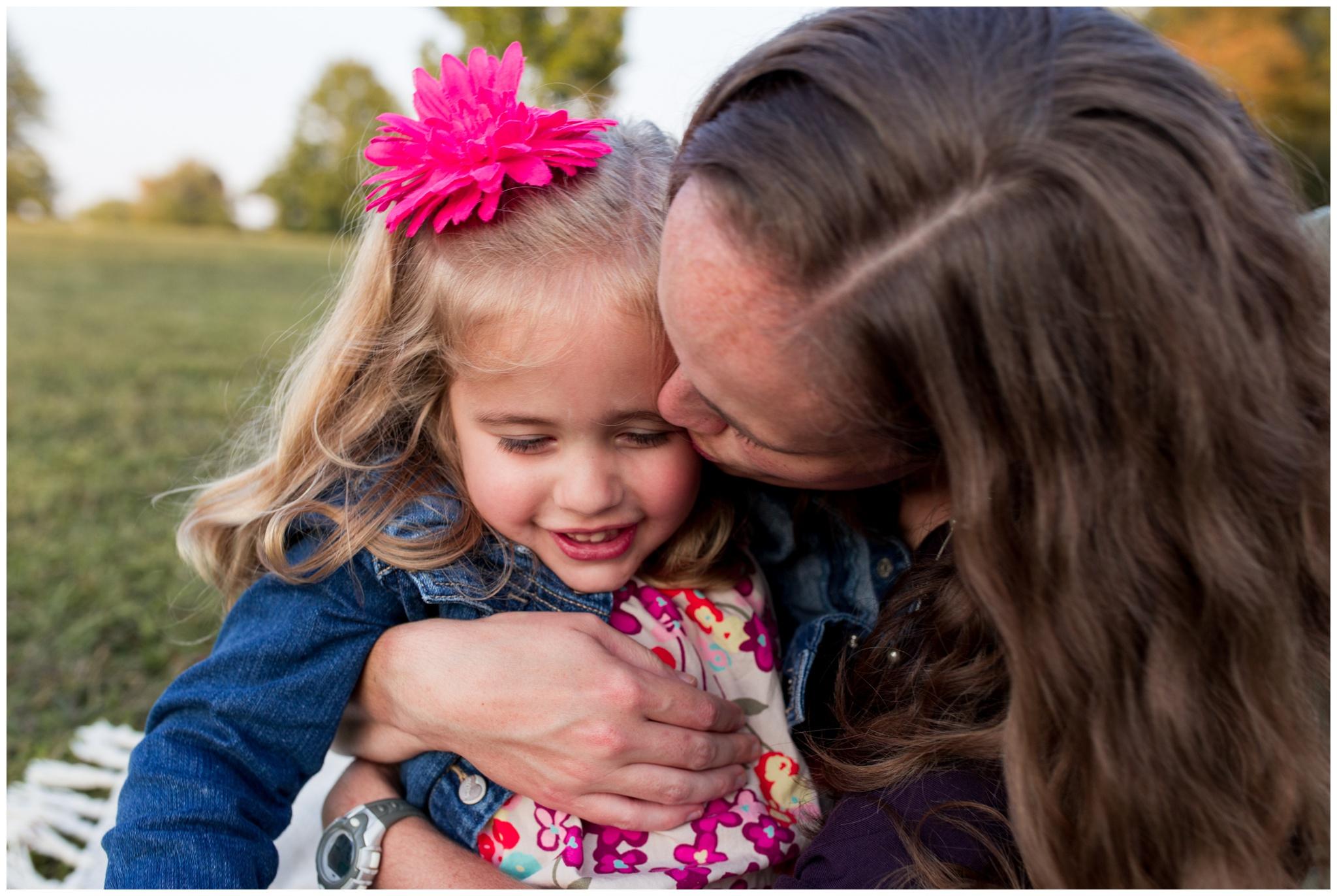 mom kissing cheek of daughter during family portraits at Wildcat Creek Reservoir Park in Kokomo Indiana