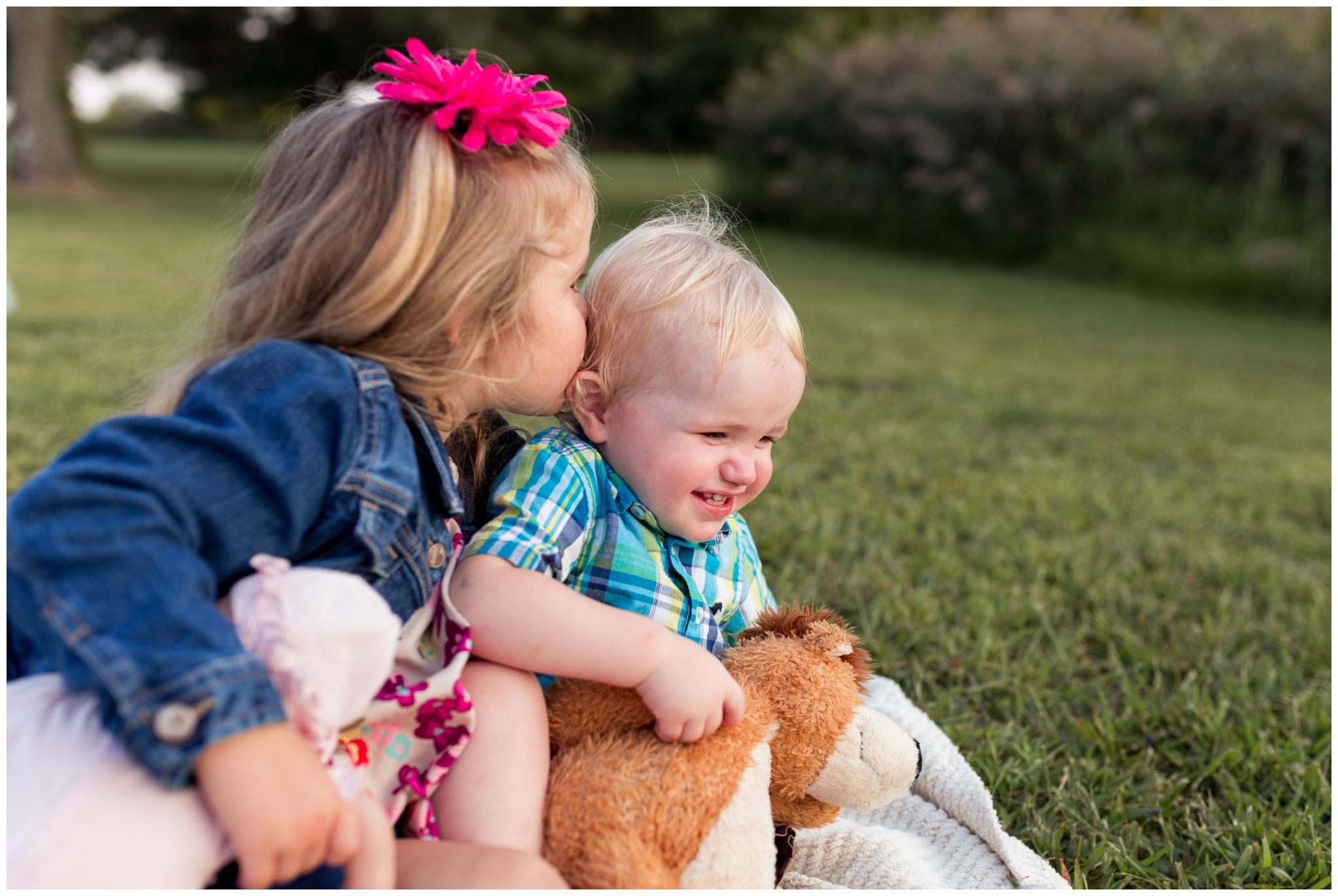 sister kisses brother's cheek during family photos at Wildcat Creek Reservoir Park in Kokomo Indiana