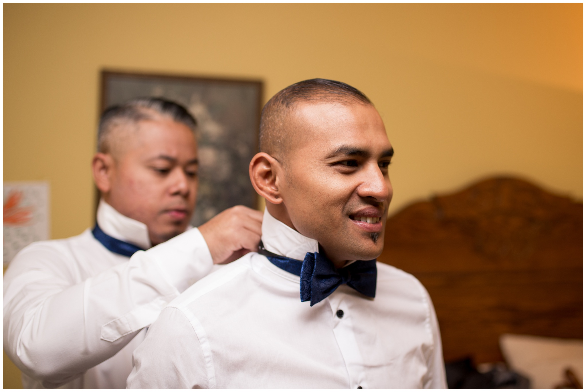 groomsman helps groom with bowtie before Romer's Catering Greenville wedding