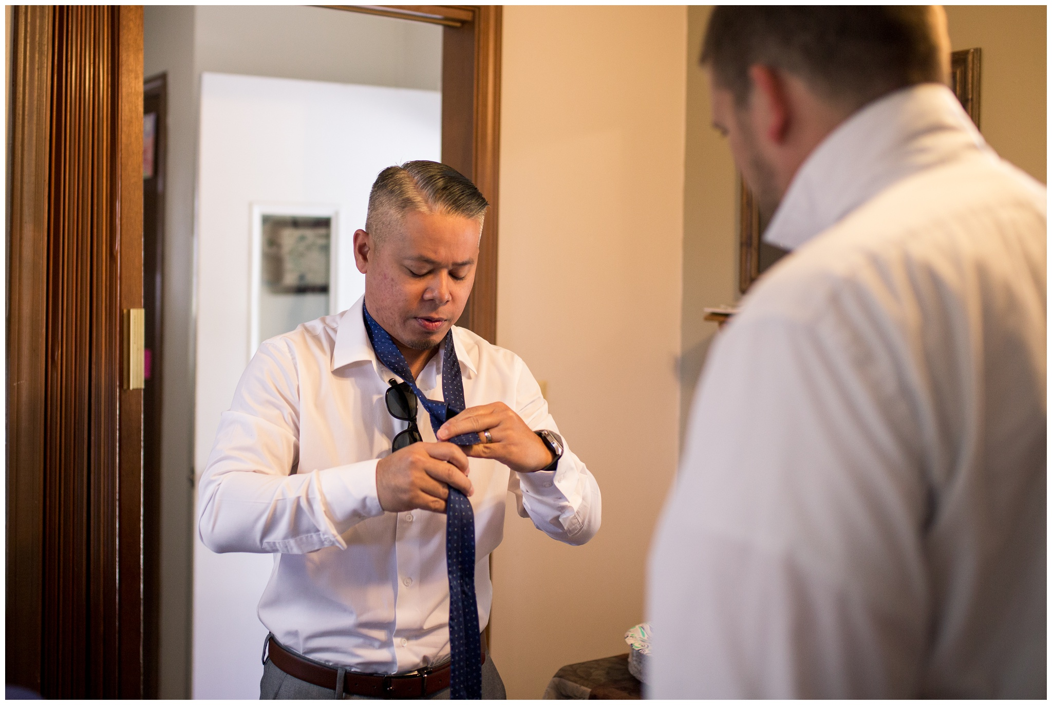 groomsman helps brother of bride with tie before wedding in Greenville Ohio