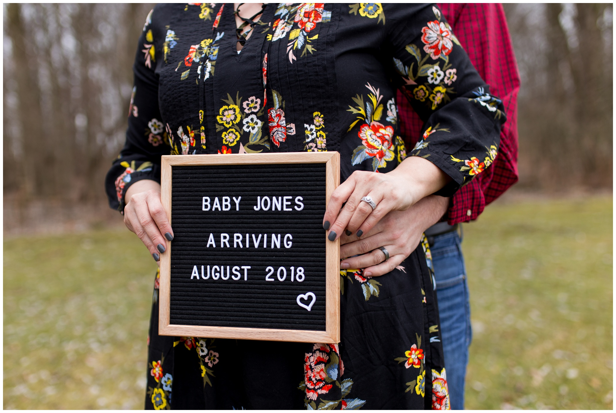husband and wife announce pregnancy with sign board