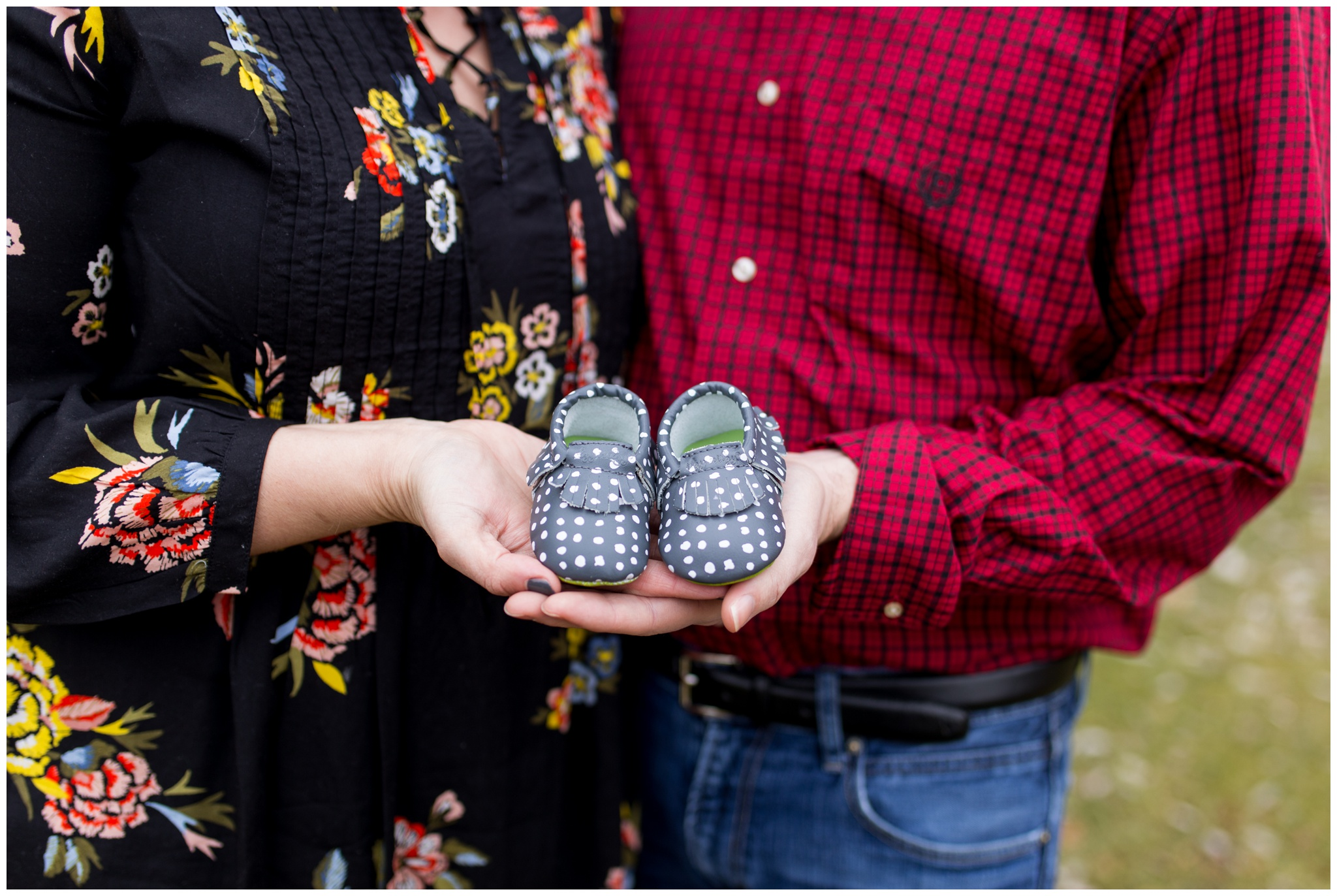 mom and dad hold baby shoes for Kokomo Indiana maternity session