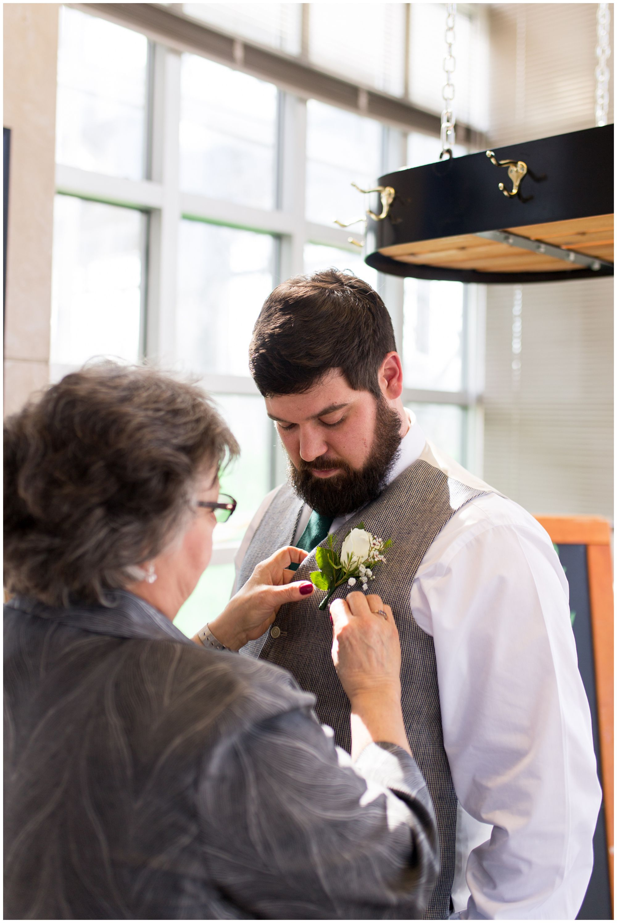 mom pins boutonniere on groom before Garfield Park Conservatory Indianapolis wedding