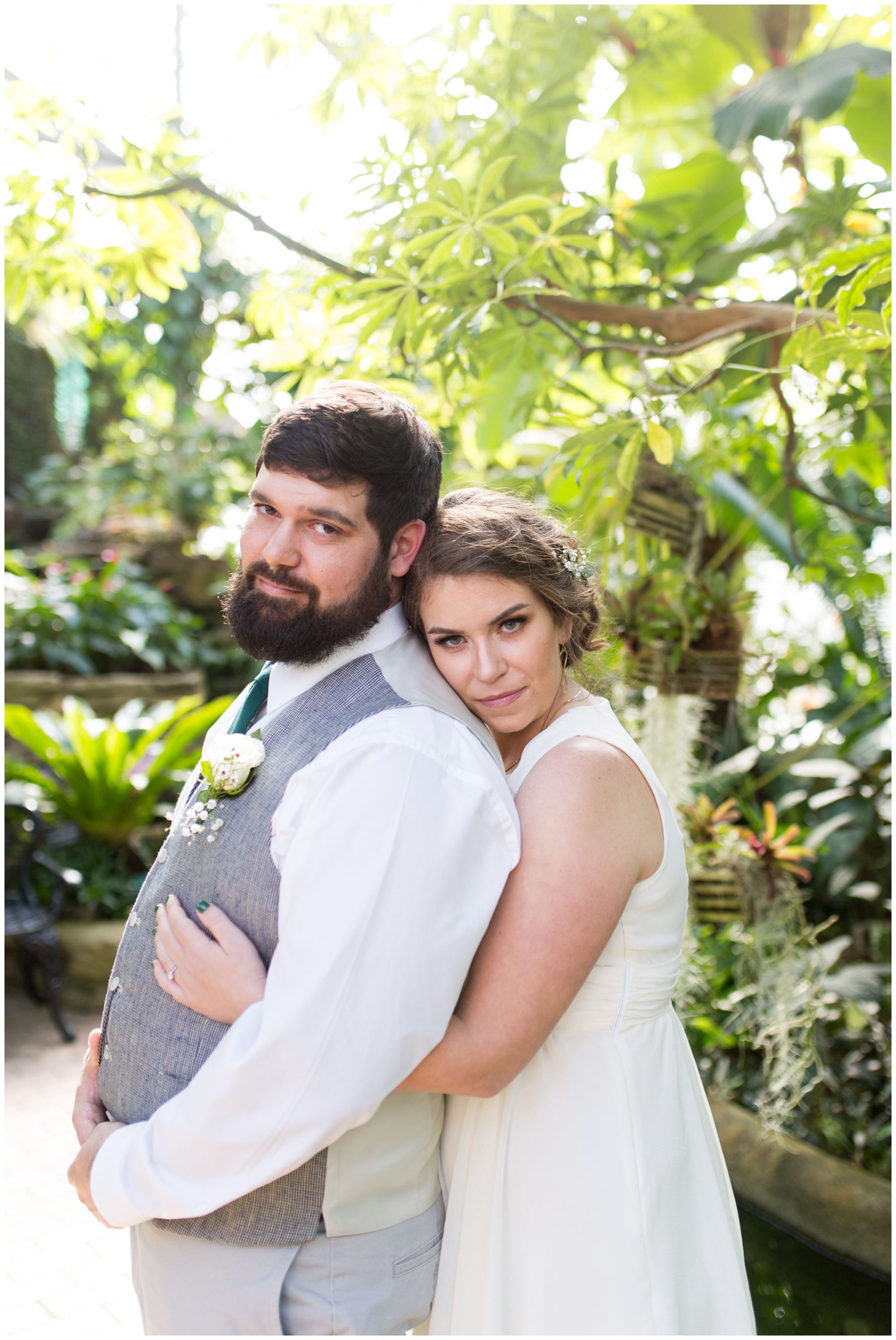bride holds groom close before Indianapolis wedding at Garfield Park Conservatory