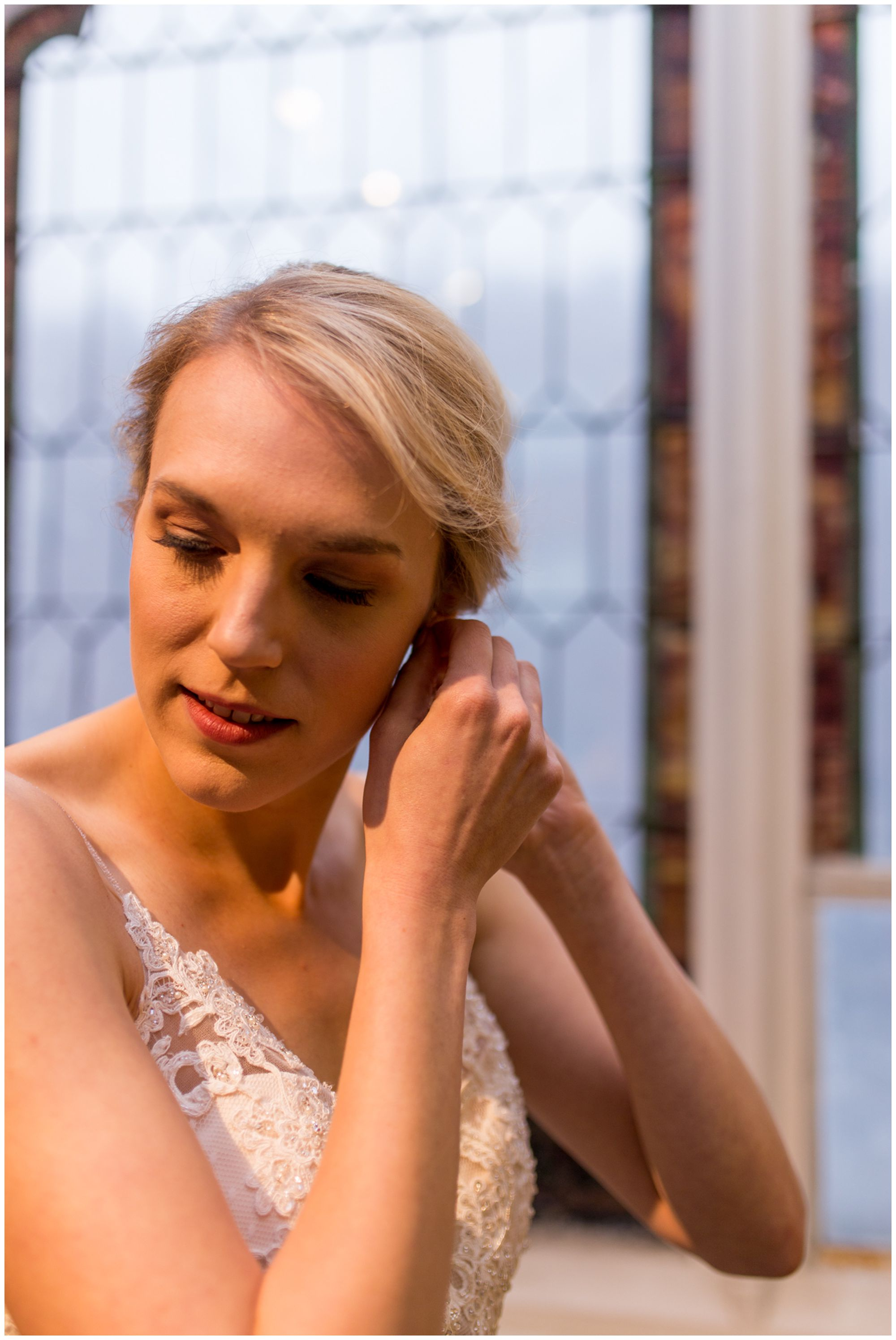 bride putting in earrings before wedding at Redeemer Presbyterian Church in Indianapolis