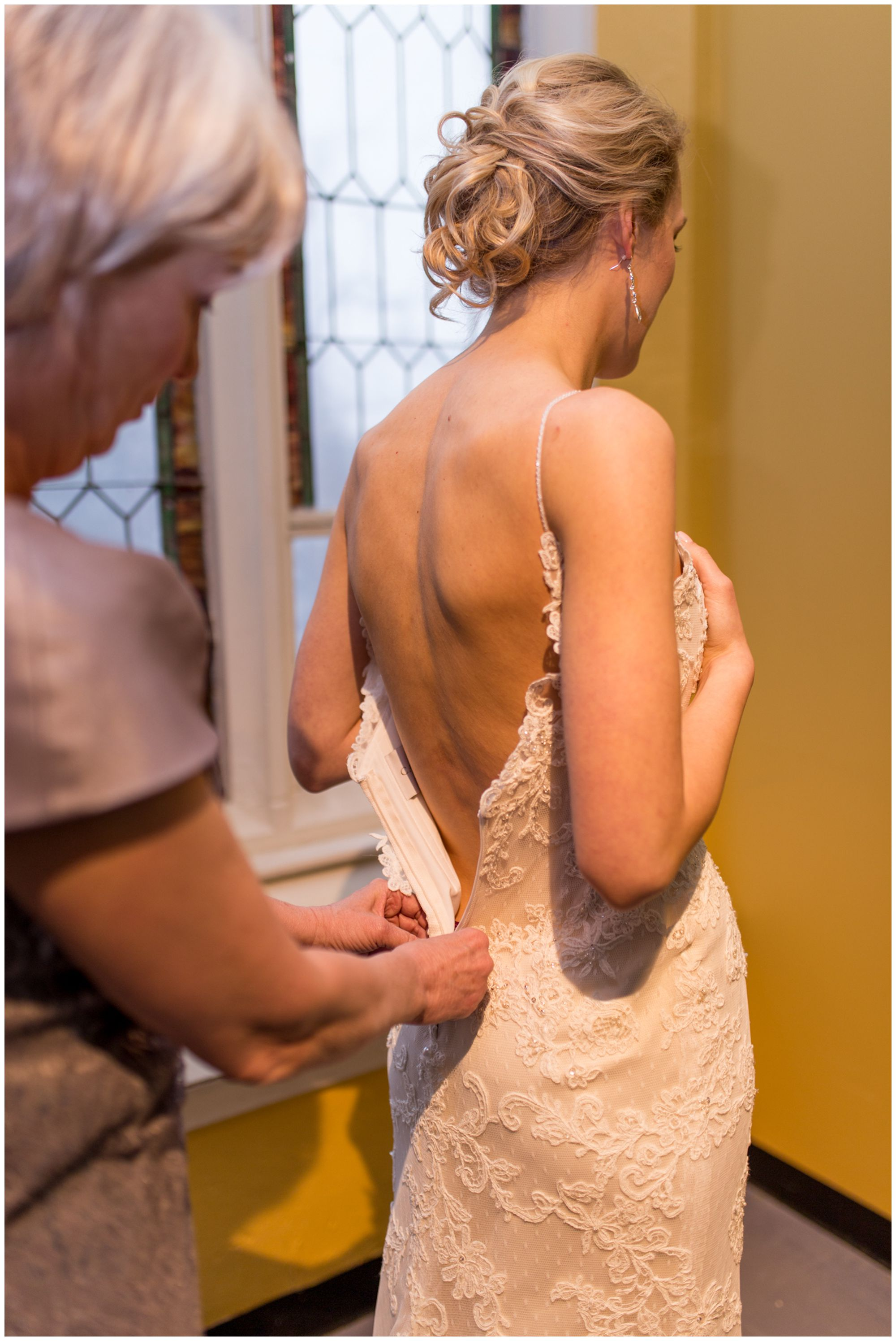 mother of the bride zipping back of bride's dress before wedding at Redeemer Presbyterian Church Indianapolis