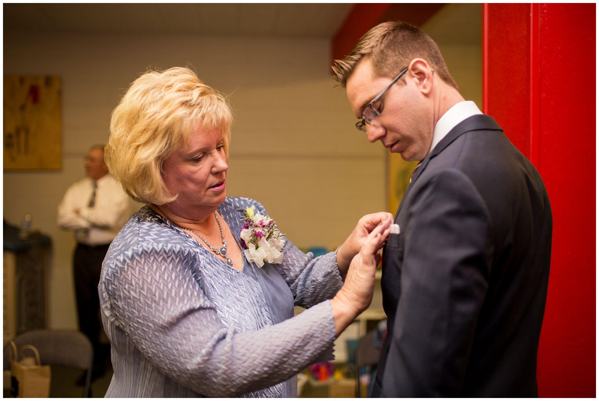 mother of groom pinning boutonniere on groom before wedding at Redeemer Presbyterian Church Indianapolis