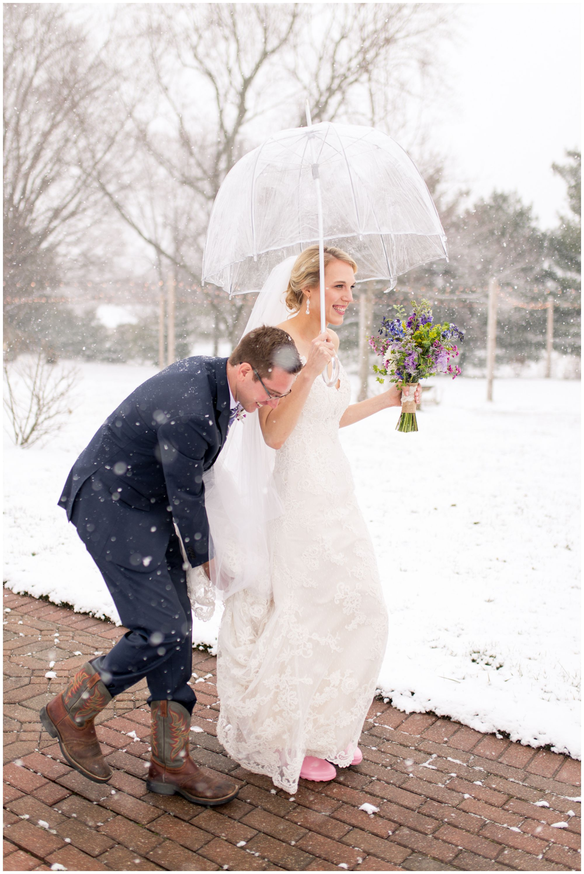 bride and groom walking in snow at Mustard Seed Gardens wedding reception in Noblesville Indiana