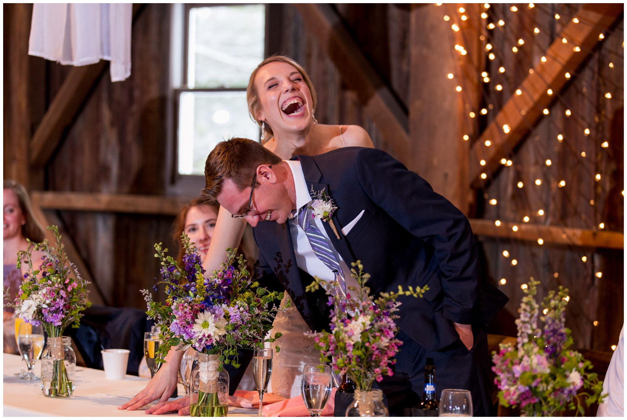 bride and groom laughing during reception toasts at Mustard Seed Gardens in Noblesville Indiana