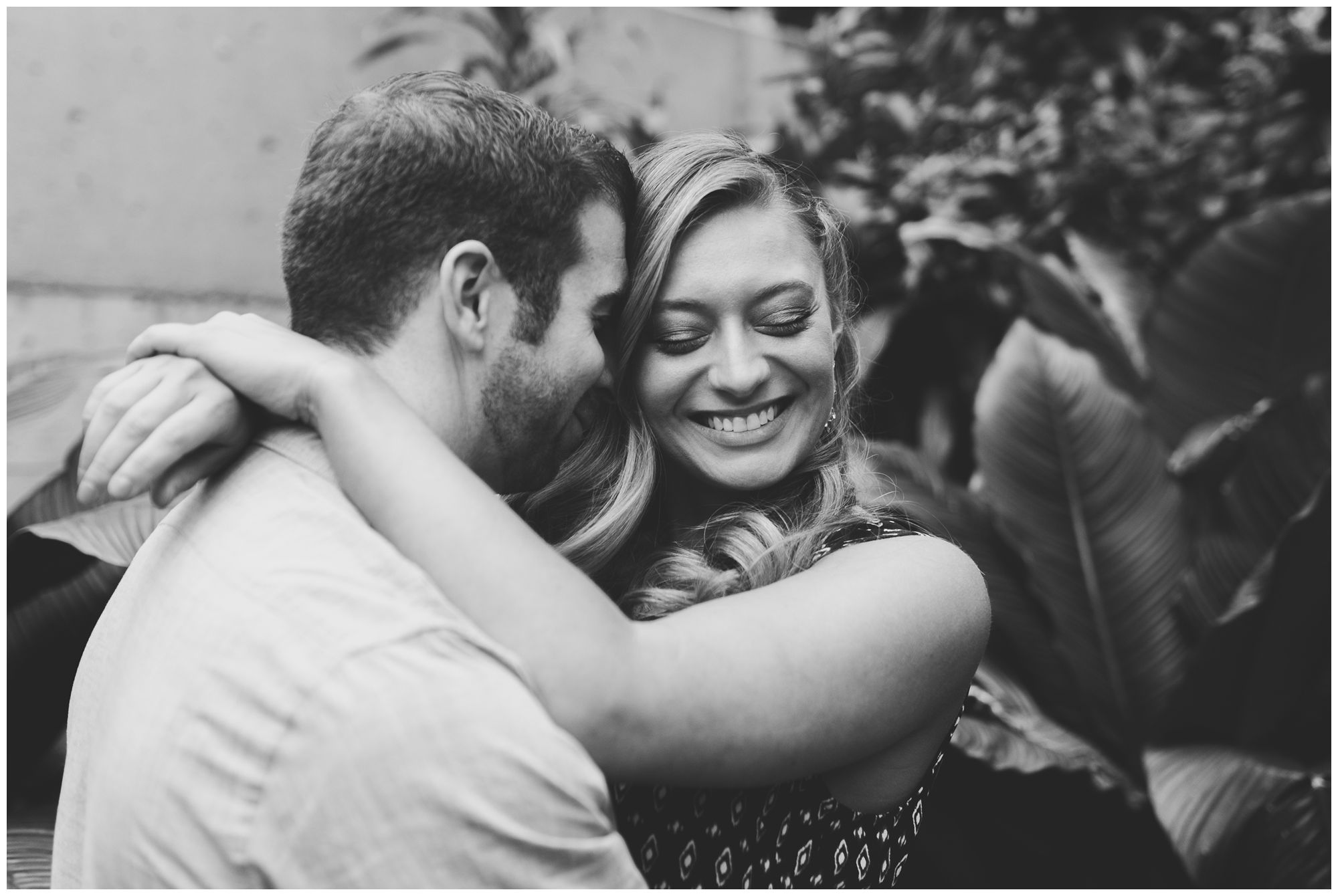 couple snuggling and laughing during engagement session at Foellinger-Freimann Botanical Conservatory in Fort Wayne Indiana