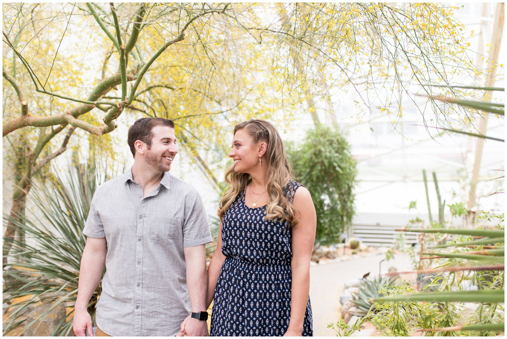 couple looks at each other during engagement session at Foellinger-Freimann Botanical Conservatory in Fort Wayne Indiana