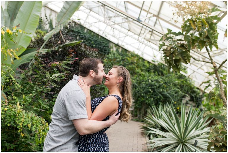couple dips for a kiss at Foellinger-Freimann Botanical Conservatory for engagement session in Fort Wayne Indiana