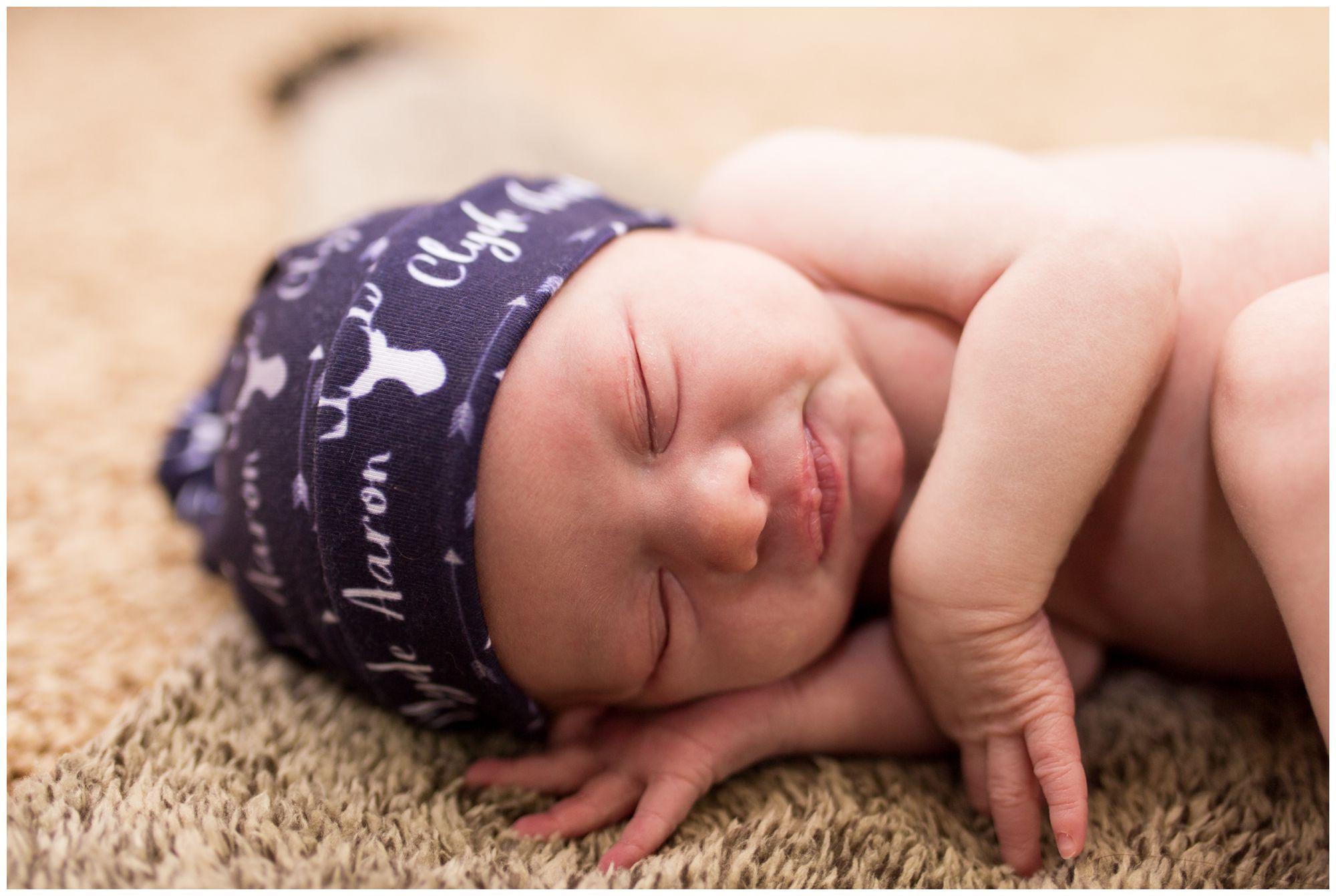 newborn smirks during Kokomo newborn session in adventure themed nursery