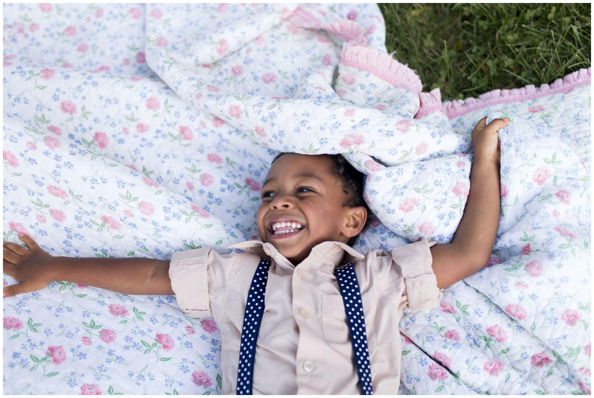 son gives cheesy smile lying on blanket at Jackson Morrow Park during Kokomo family session