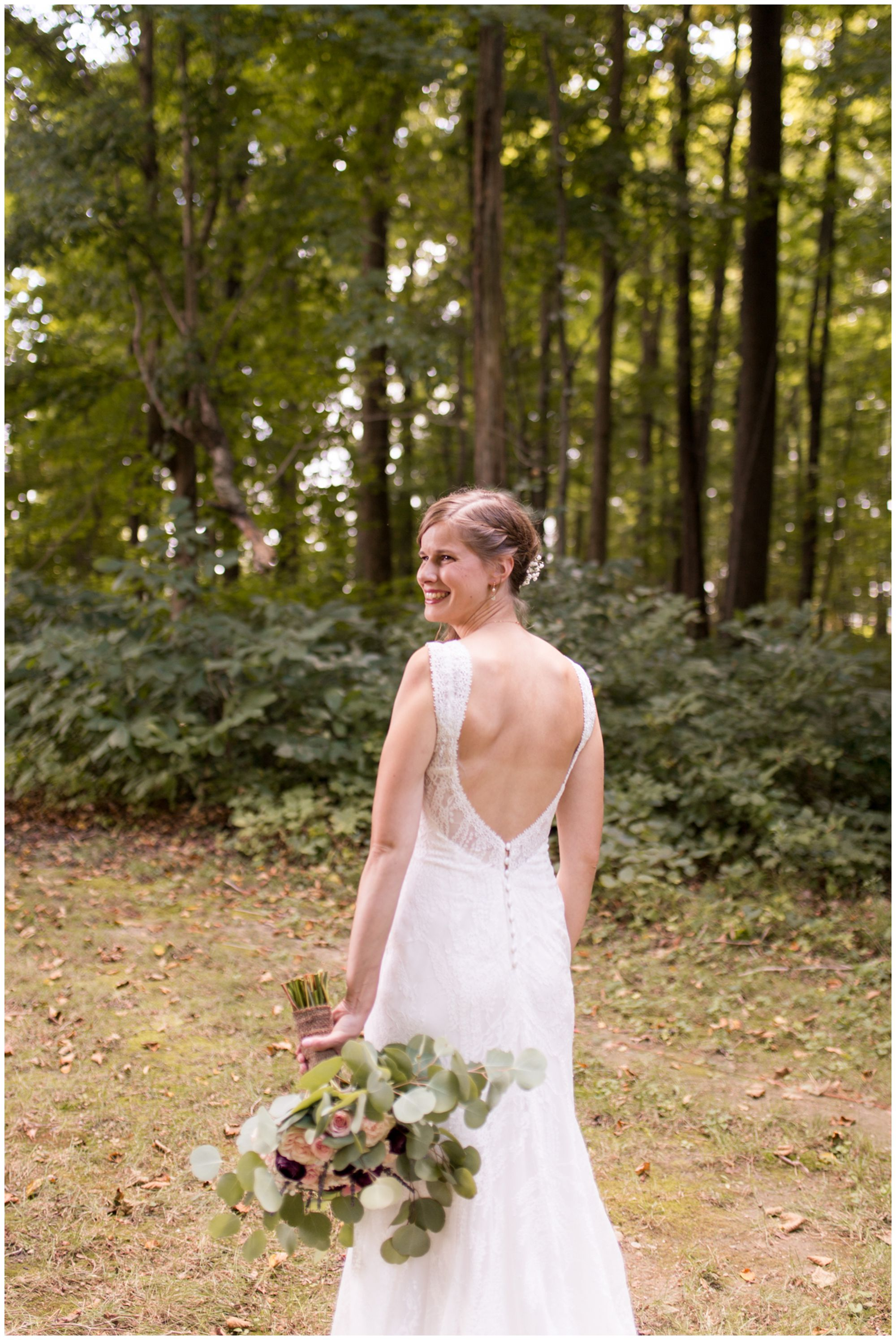 bride Tabea holds bouquet in left hand and looks back over left shoulder smiling at Kokomo wedding photographer