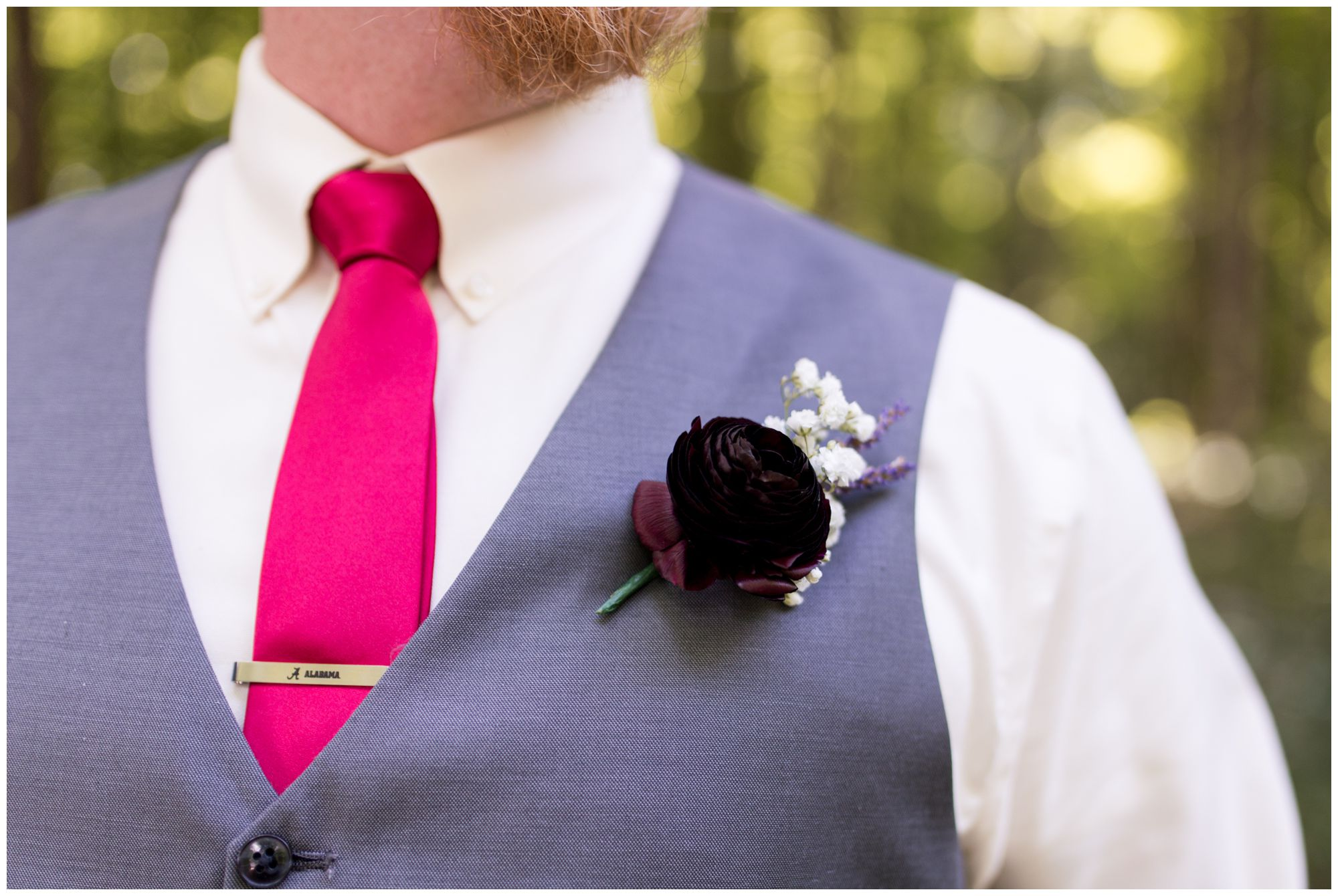close up of groom Daniel's Alabama tie clip and boutonniere
