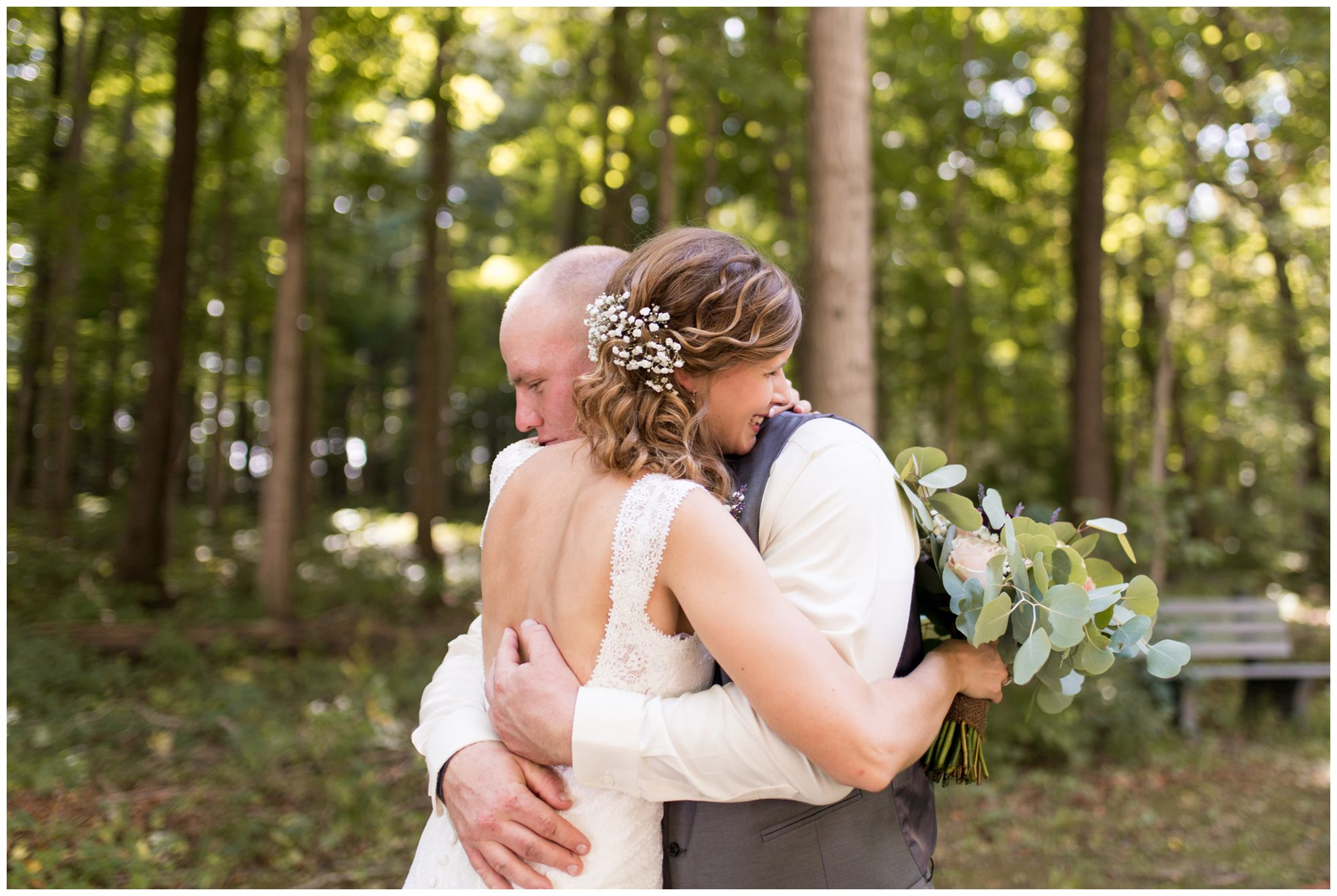 bride Tabea and groom Daniel hug during wedding portraits in woods at Crossroads Community Church