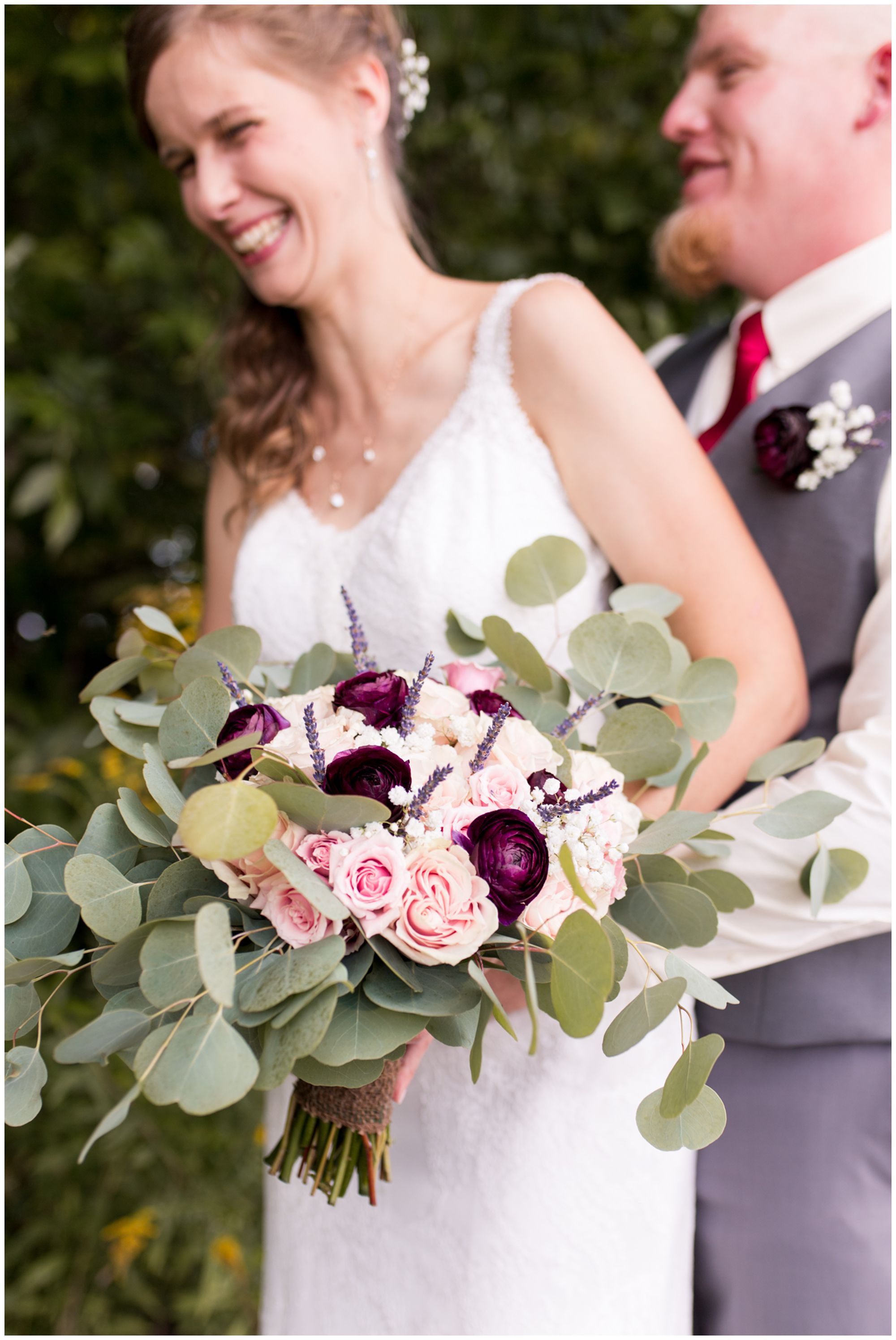 close up of bride's bouquet while bride Tabea and groom Daniel laugh in background at Crossroads Community Church