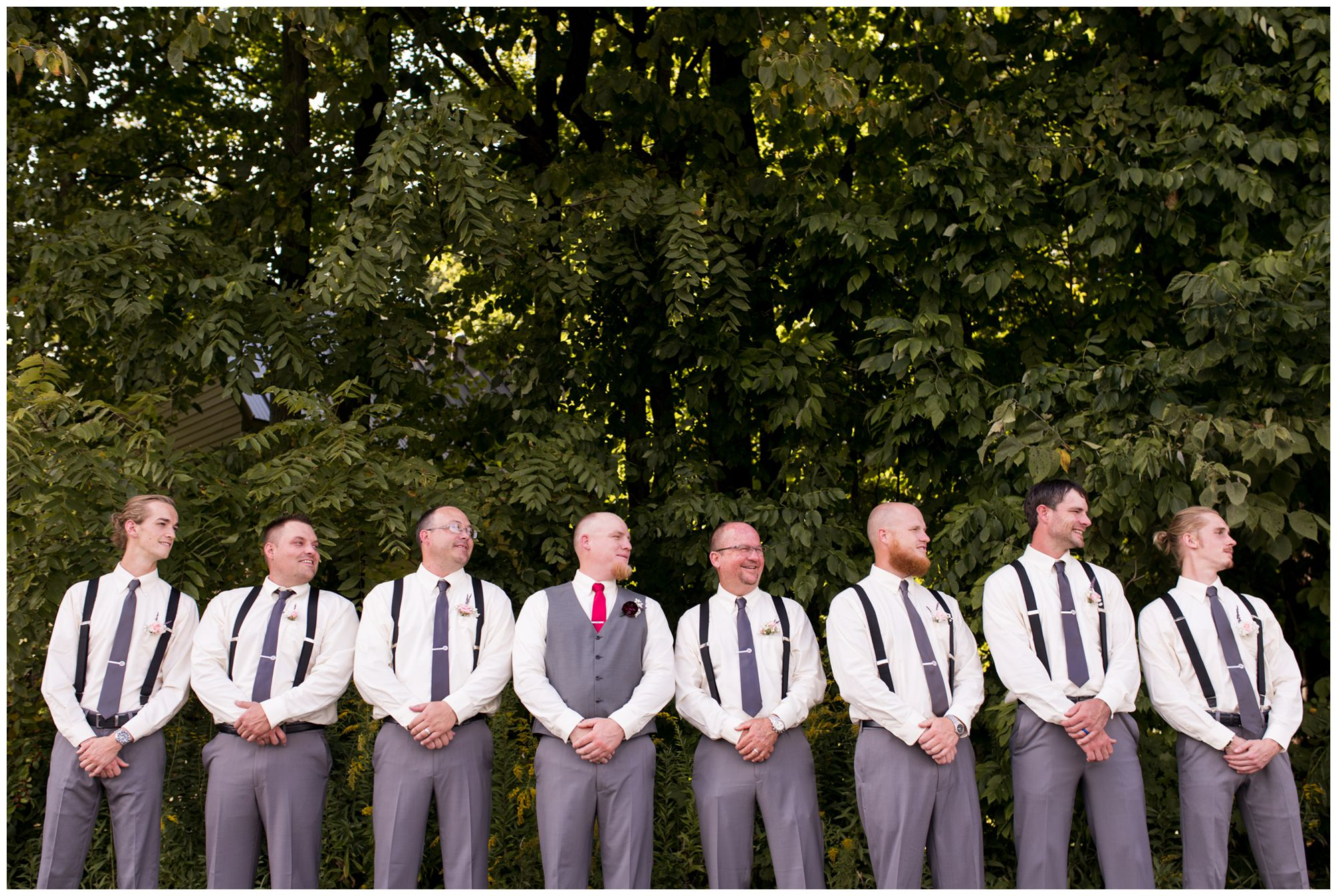 groom and groomsmen stand in line looking over left shoulder with camera pointing up at them